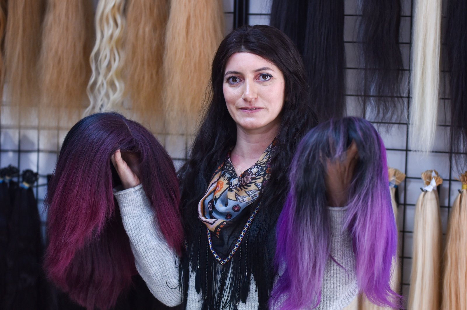 A woman holds two different styles of wigs in a wig store, Antalya, Turkey, Jan. 27, 2021. (DHA Photo)