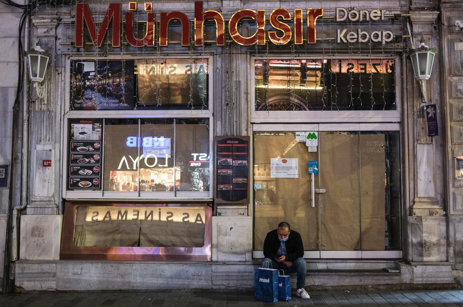 A man wearing a mask sits in front of the closed Turkish Kebap-Döner restaurant on Istiklal Avenue in Istanbul, Turkey, Jan. 22, 2021. (EPA Photo)