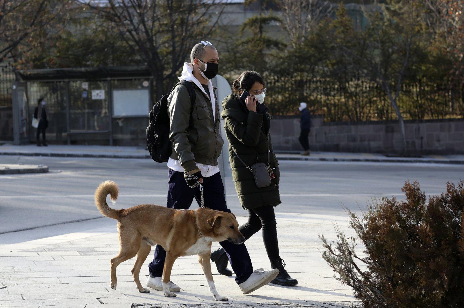 A couple wearing mask walk their dog on a street in the capital Ankara, Turkey, Jan. 22, 2021. (AP Photo)