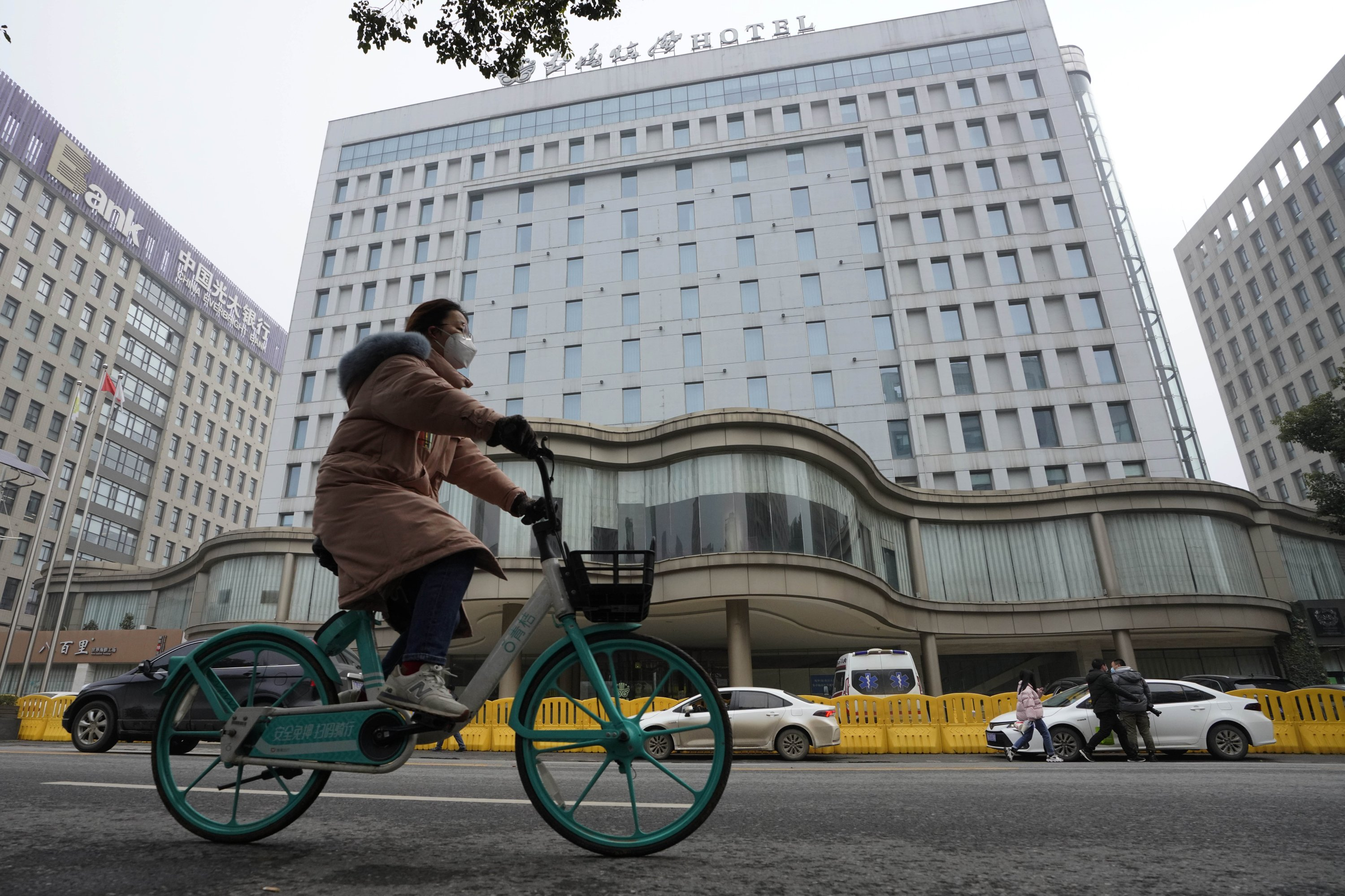 A cyclist rides by the hotel where a team of experts from the World Health Organization (WHO) quarantined in Wuhan, central Hubei province, China, Jan. 28, 2021. (AP Photo)