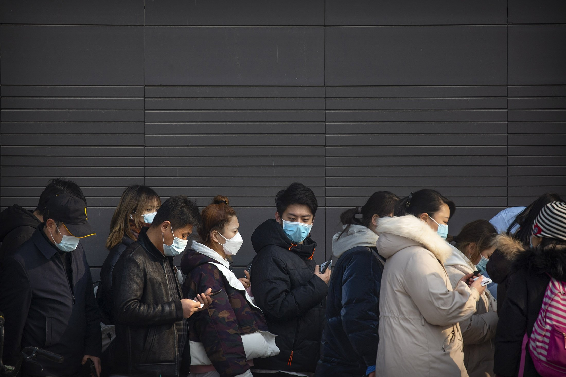 People wearing face masks to protect against the spread of the coronavirus line up for mass COVID-19 testing in a central district of Beijing, Jan. 22, 2021. (AP Photo)