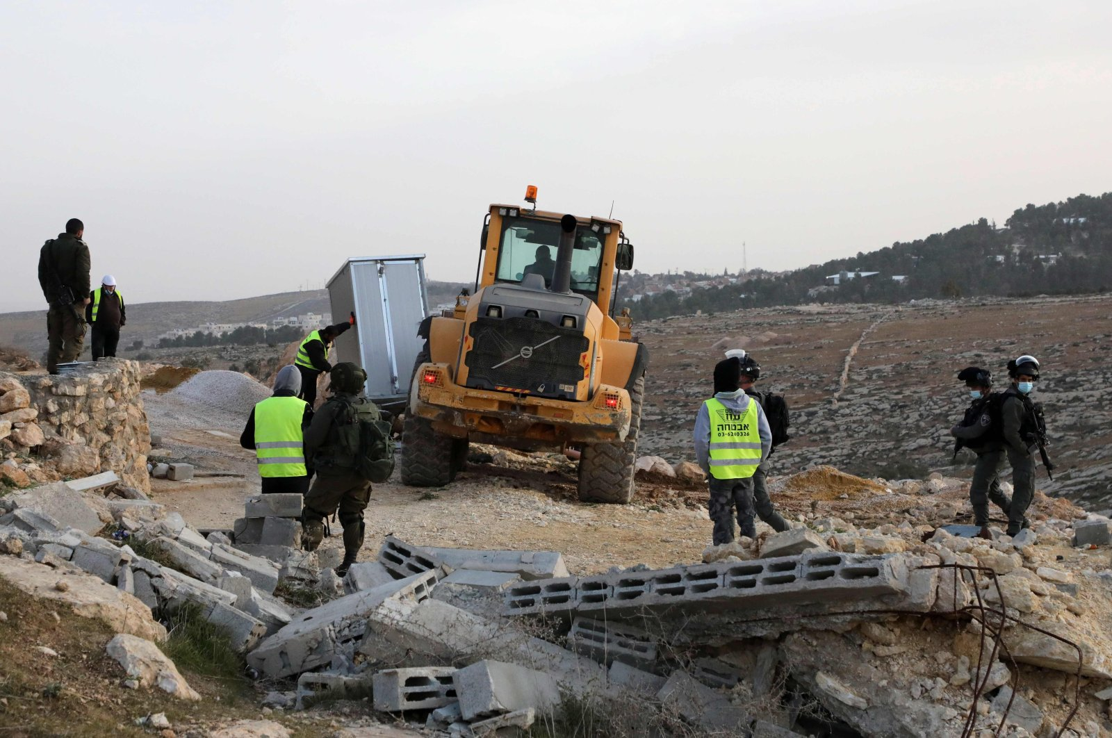 Israeli security forces gather as an army bulldozer removes a structure in the village of al-Mufagara, near Yatta, south of Hebron in the occupied West Bank, Palestine, Jan. 27, 2021. (AFP Photo)