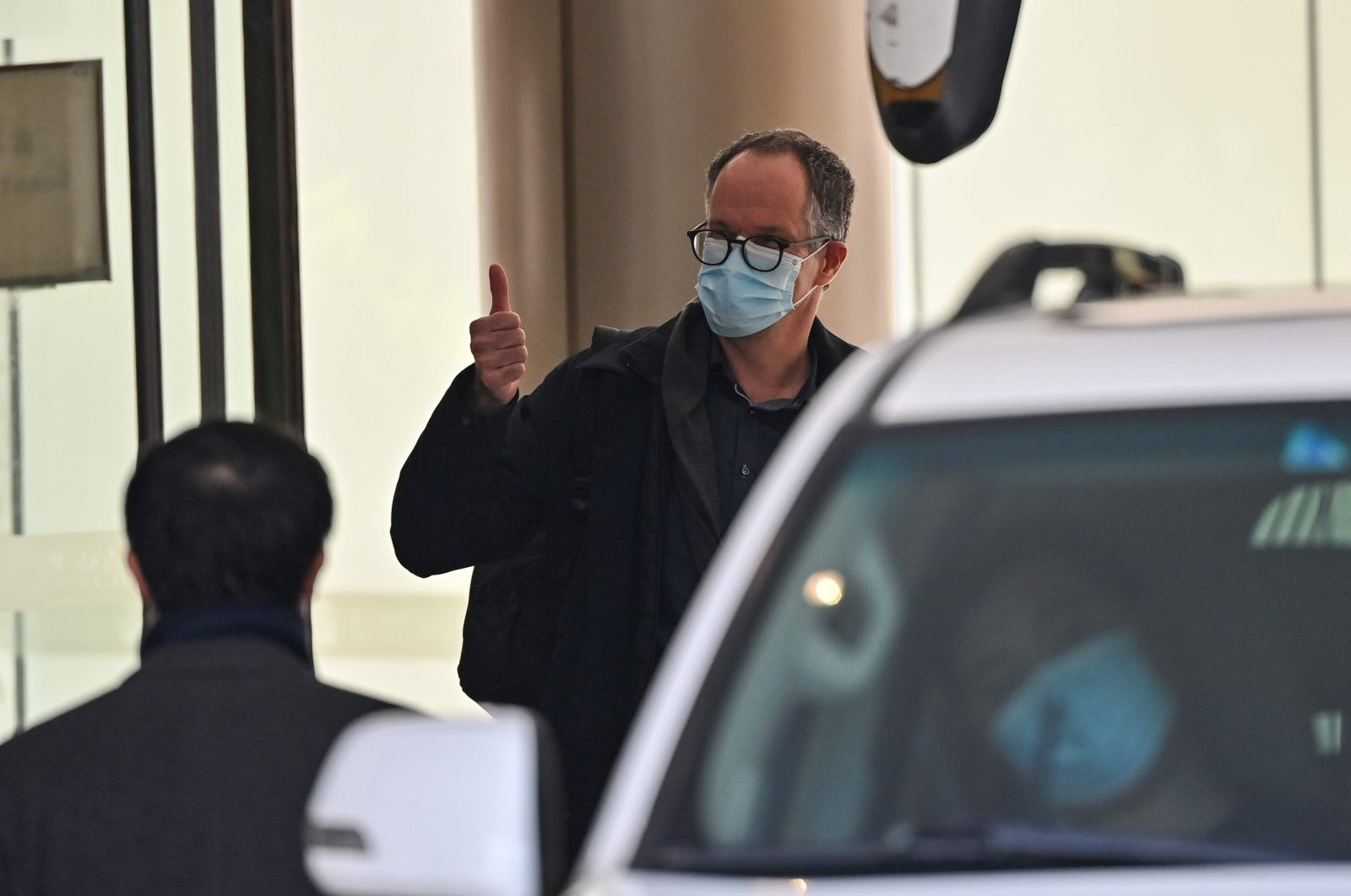 One of the members of the World Health Organization (WHO) team investigating the origins of the coronavirus pandemic gives a thumbs-up as he leaves The Jade Hotel after completing quarantine in Wuhan, central Hubei province, China, Jan. 28, 2021. (AFP Photo)