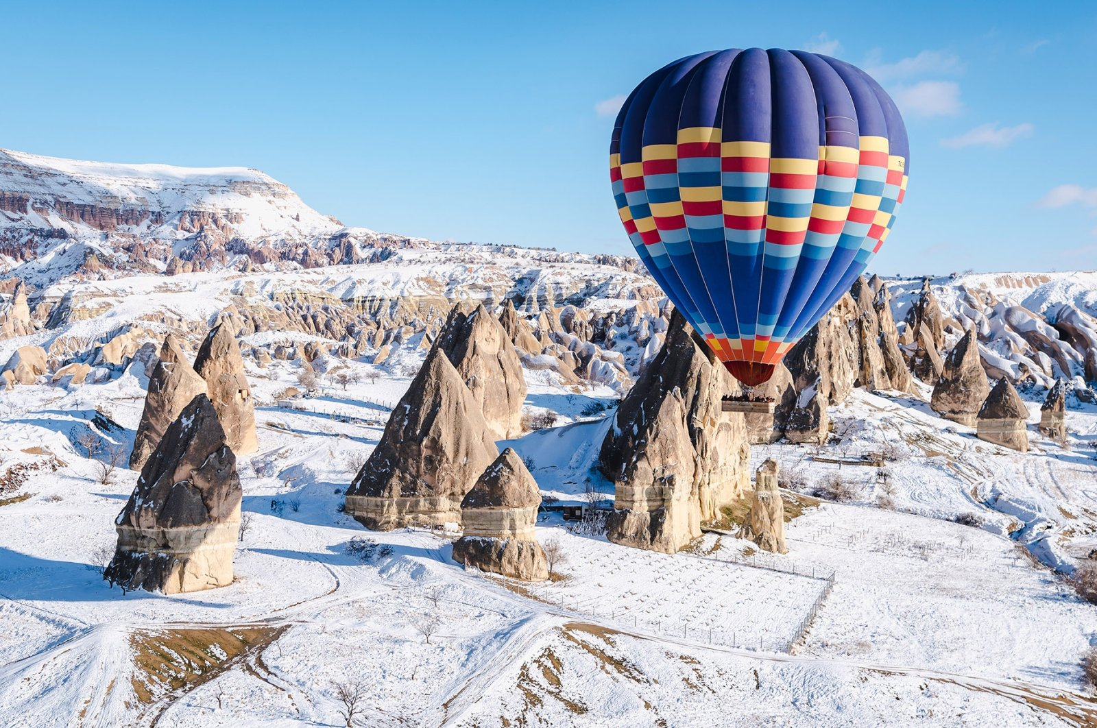 Going on a hot air balloon ride over snowy mountains in Cappadocia is a magical experience. (Shutterstock Photo)