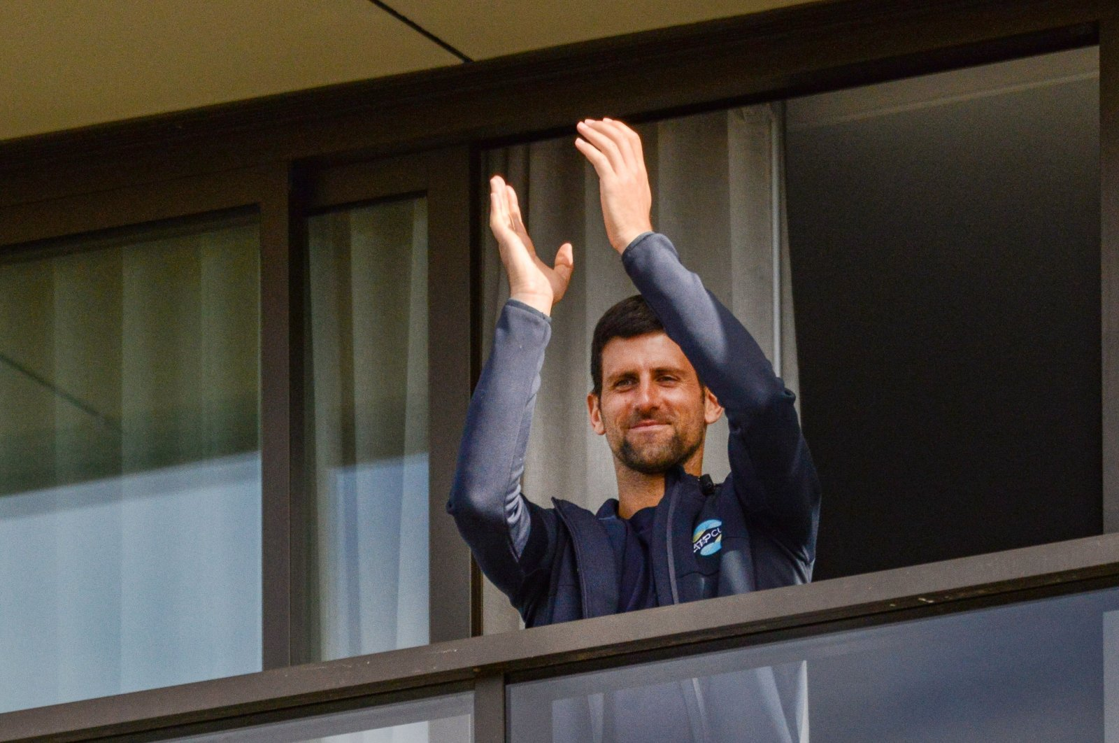 Men's world No. 1 tennis player Novak Djokovic of Serbia gestures from his hotel balcony on the last day of his mandatory two-week quarantine in Adelaide, Australia, Jan. 28, 2021. (Photo by Brenton Edwards via AFP)