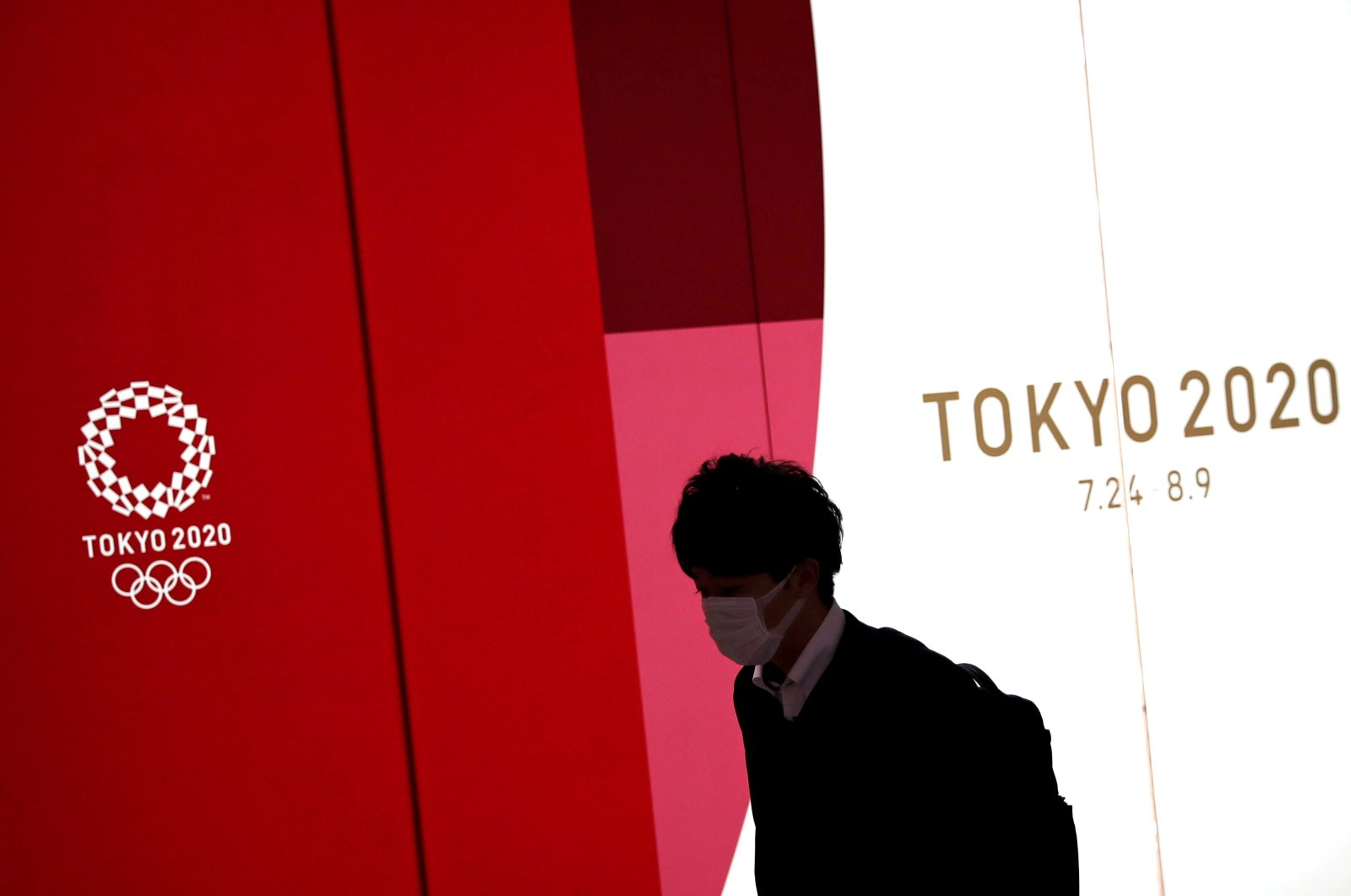 A man wearing a protective face mask during the COVID-19 walks past the upcoming Tokyo 2020 Olympics decoration board in Tokyo, Japan, March 23, 2020. (Reuters Photo)