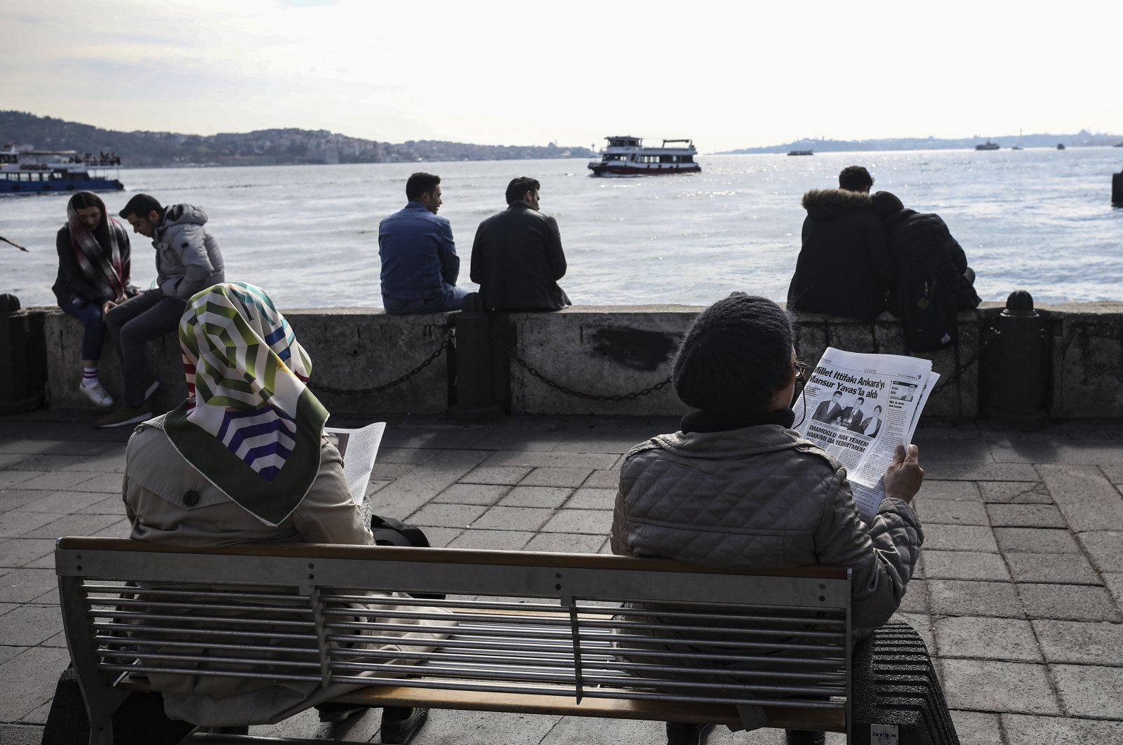 People sit reading newspapers that contain information regarding local elections a day after the vote, next to the Bosporus in Istanbul, Turkey, April 1, 2019. (AP Photo)