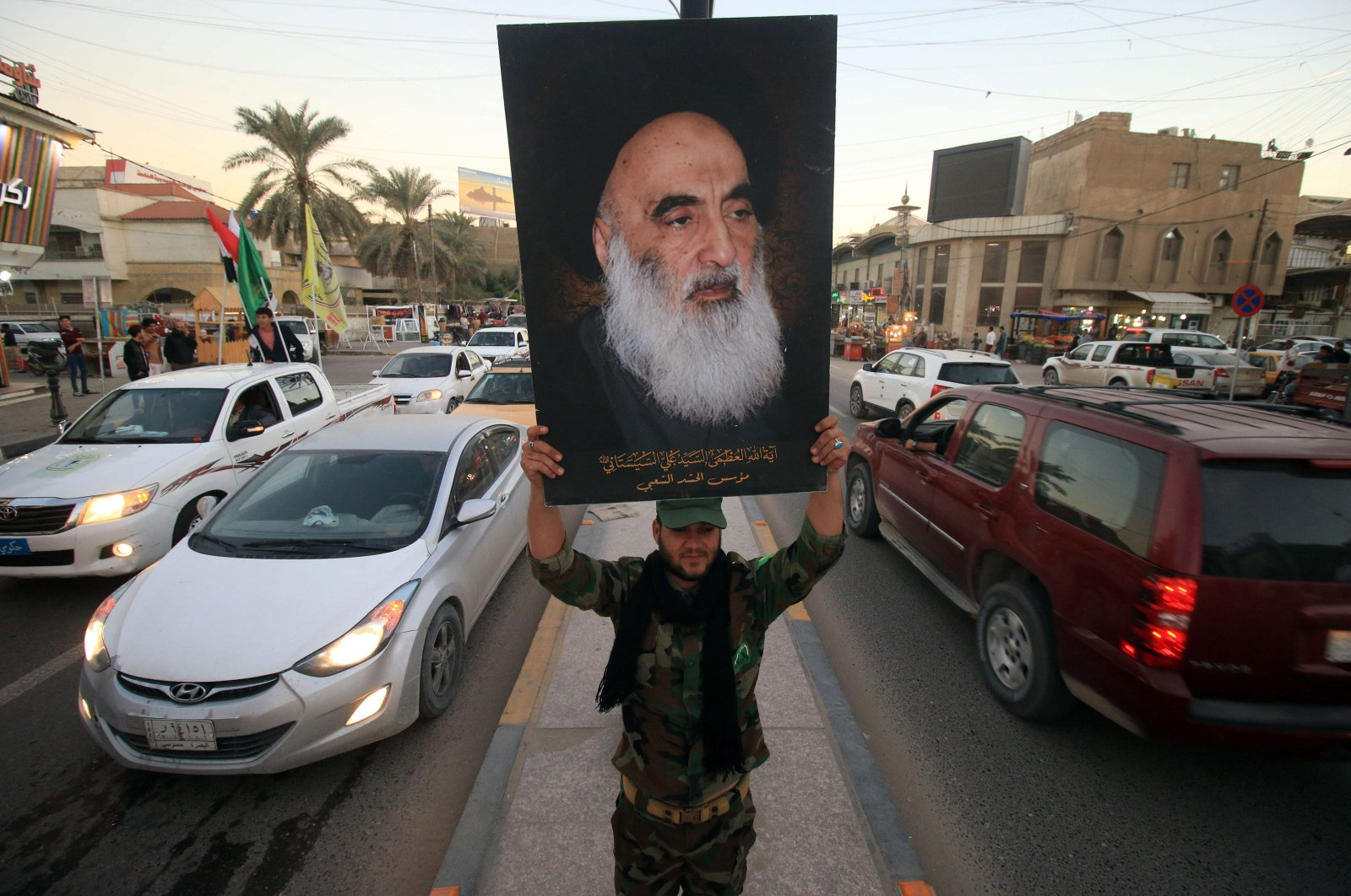 In this file photo a member of the Hashed al-Shaabi (Popular Moblisation units) carries a portrait of Iraqi Shiite cleric Grand Ayatollah Ali al-Sistani in a street in the southern city of Basra, Dec. 10, 2017. (AFP Photo)