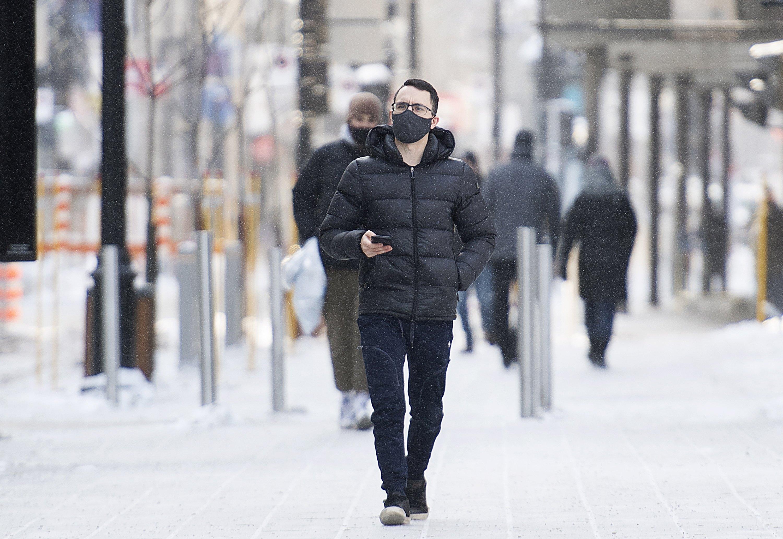 A man wears a mask as he walks along a street in Montreal, Canada, Jan. 23, 2021. (AP Photo)
