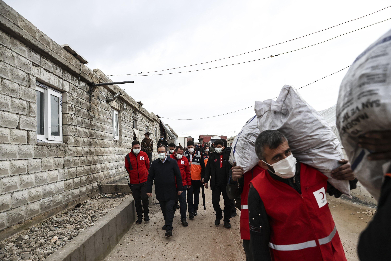 Türk Kızılayı yetkilileri, 28 Ocak 2021, Suriye'nin İdlib kentinde yeni inşa edilen evlere yardım çantaları taşıyor (AA Fotoğrafı)