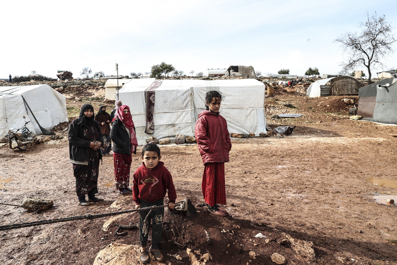 28 Ocak 2021, Suriye'nin İdlib kentinde yerinden edilmiş Suriyeliler çadırlarının önünde duruyor (AA Fotoğrafı)
