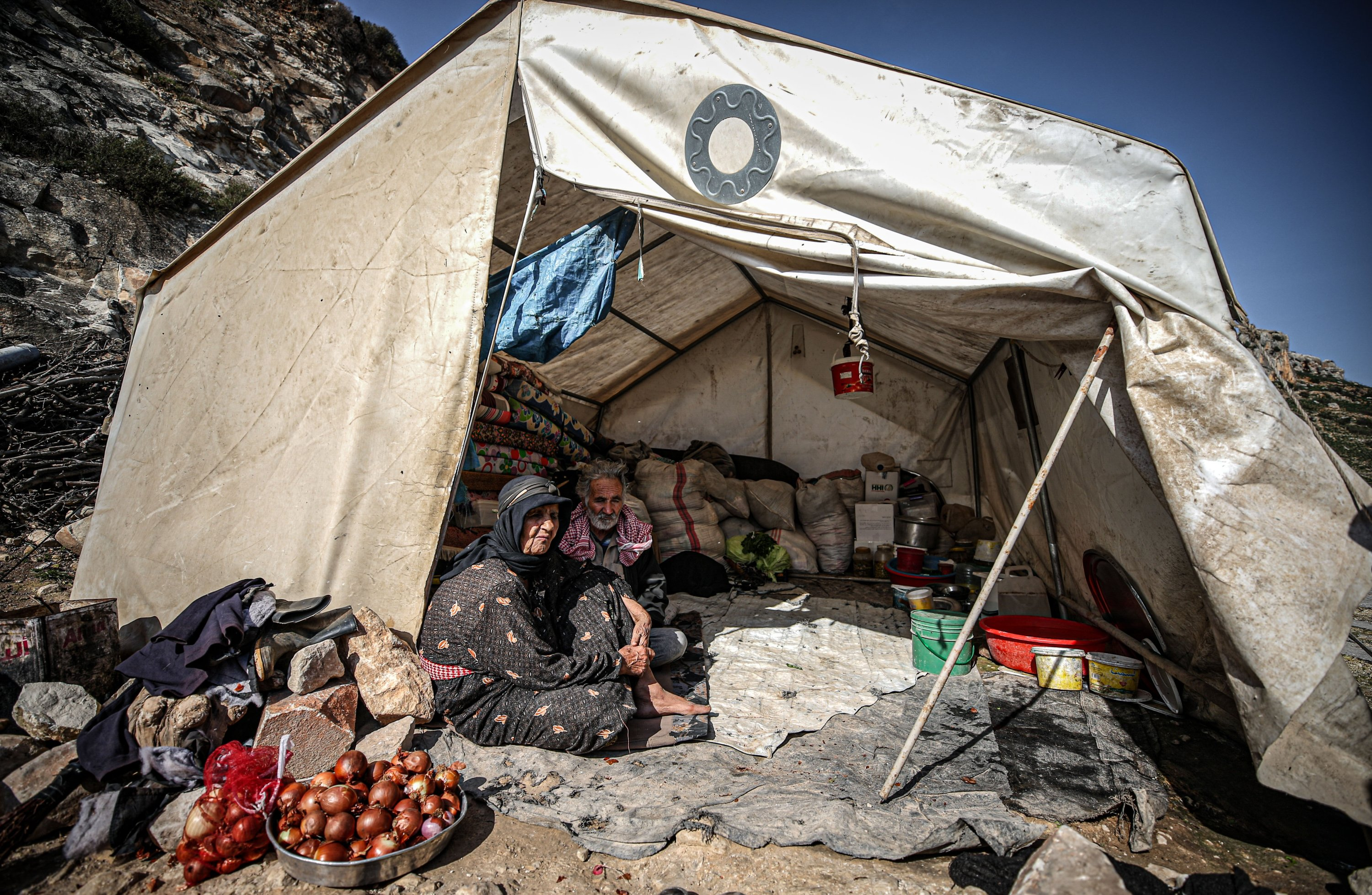 A Syrian family sits in a tent in the Sheik Isa tent camp, located close to the Orontes (Asi) River, Jan. 29, 2021. (AA)