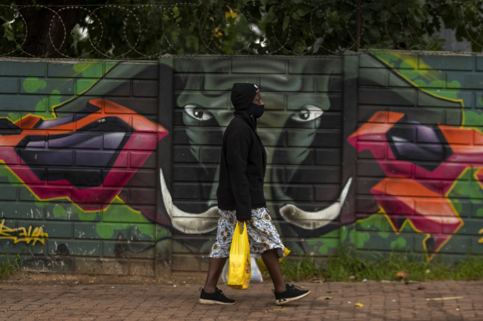 A woman wearing a face mask as a precaution against the coronavirus outbreak walks on the street in downtown Johannesburg, South Africa, Jan. 26, 2021. (AP Photo)