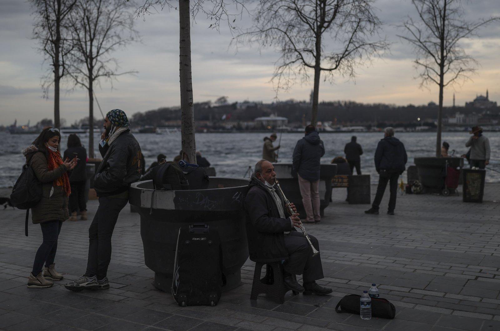 A musician performs while people promenade at the seaside of Karaköy, Beyoğlu, Istanbul, Turkey, Jan. 22, 2021. (AP Photo)