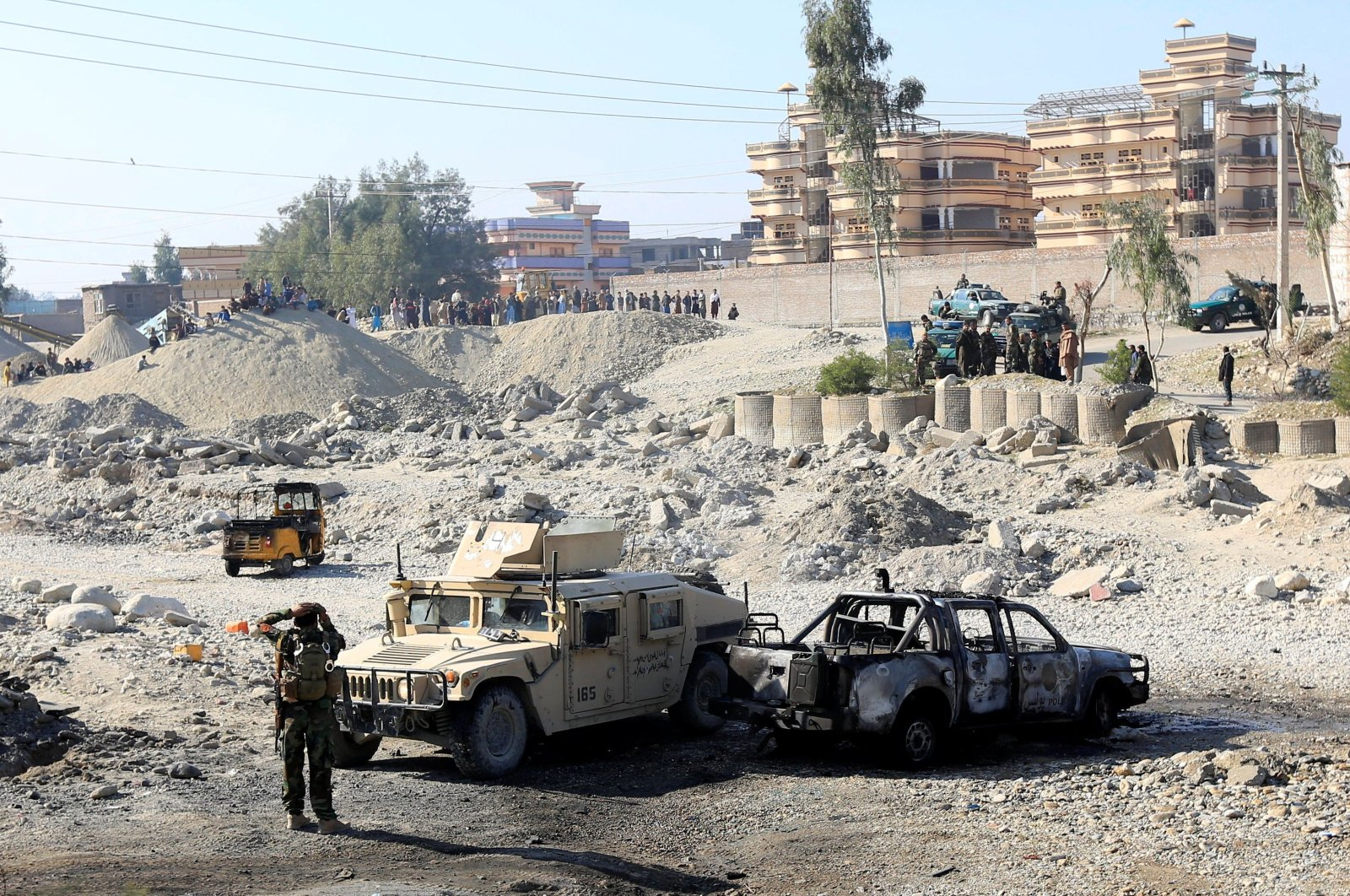 An Afghan National Army soldier inspects the wreckage of a burnt army car at the site of a blast in Jalalabad, Afghanistan, Jan. 28, 2021. (Reuters Photo)