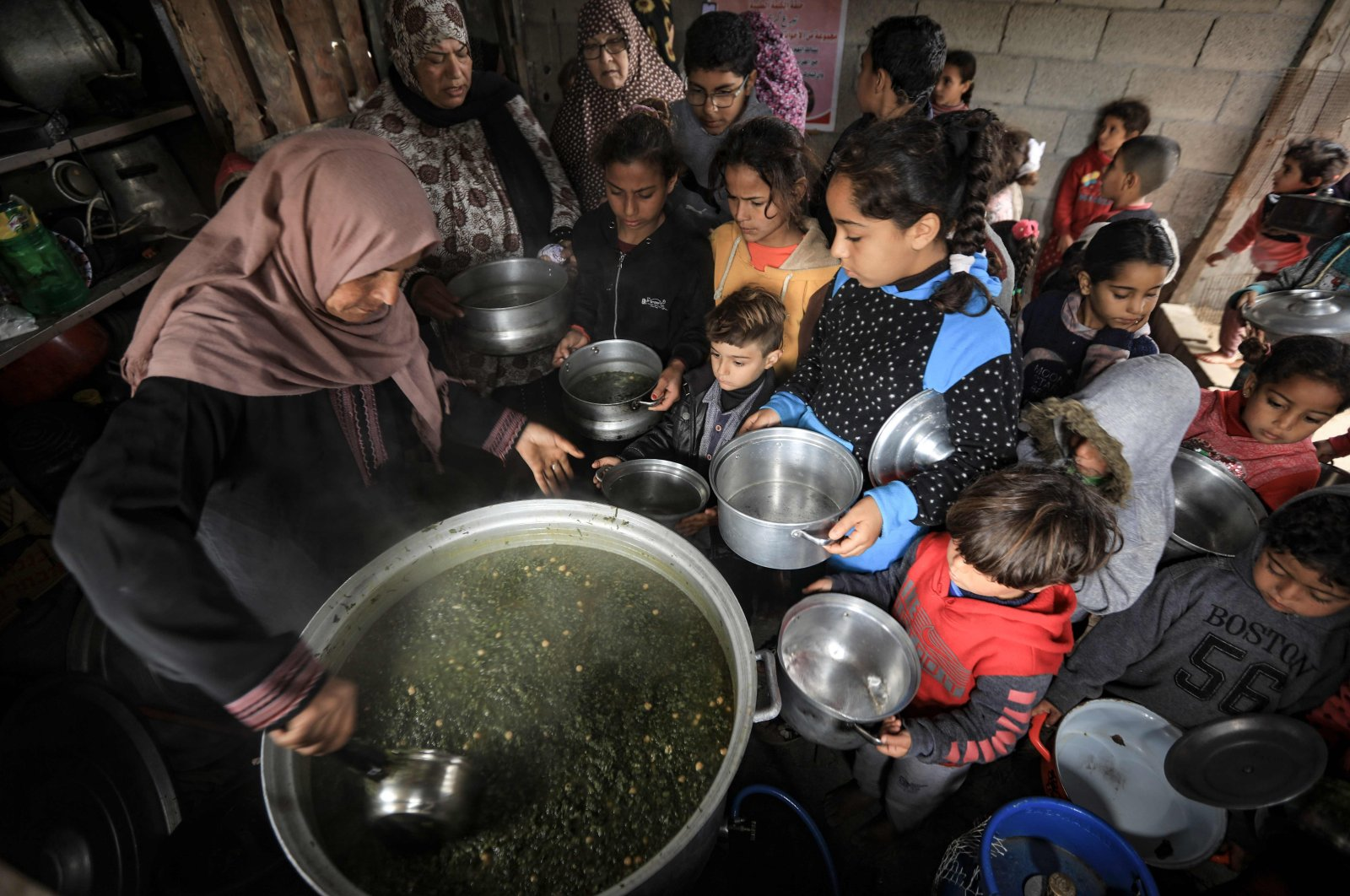 A Palestinian volunteer cook distributes food prepared with ingredients obtained from donors, to help needy families in an impoverished neighborhood in besieged Gaza City, Palestine, Jan. 28, 2021. (AFP Photo)