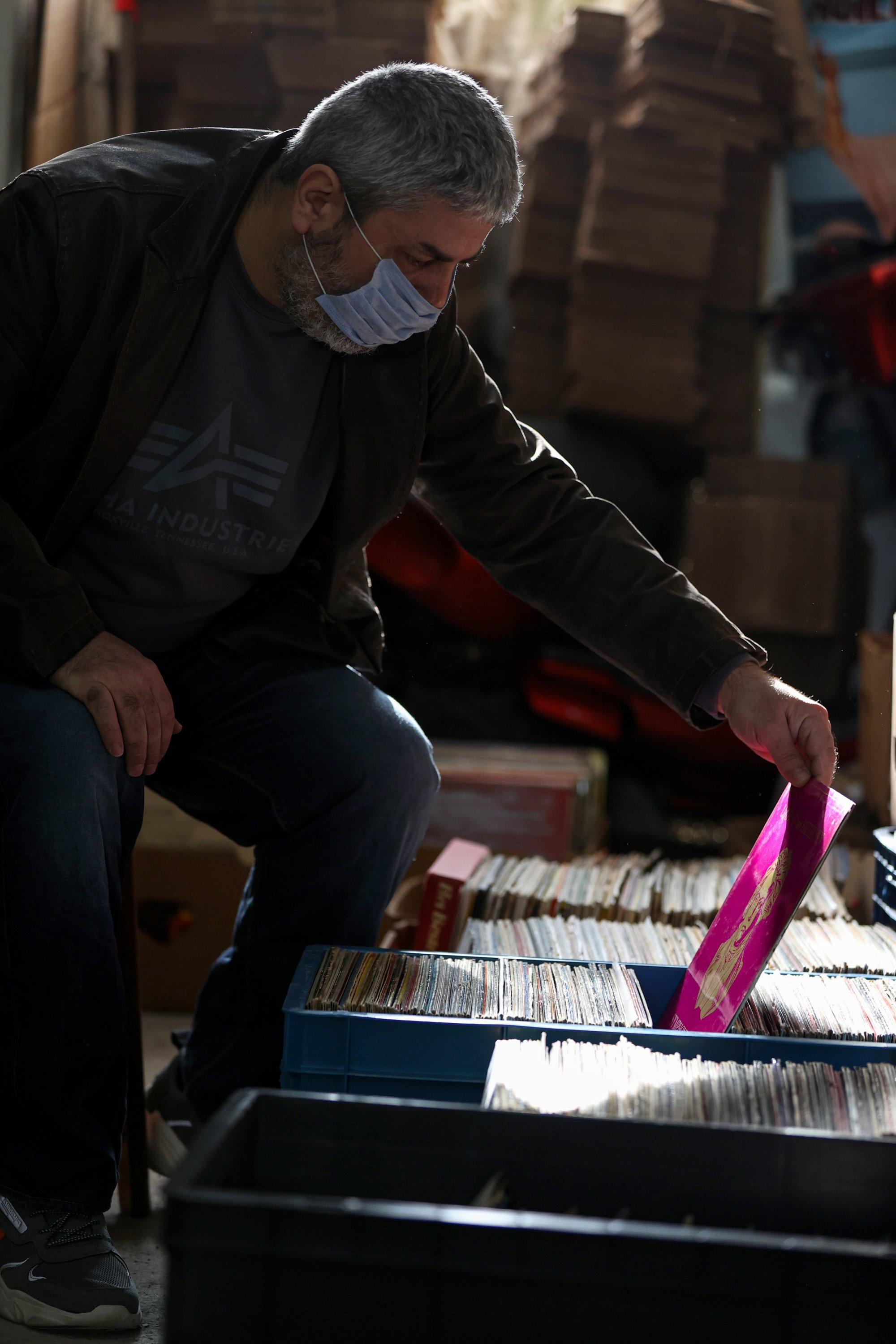 Vedat Ispir, a shopkeeper of vinyl records, picks up a record in his shop in Istanbul, Turkey, Jan. 28, 2021. (AA Photo)