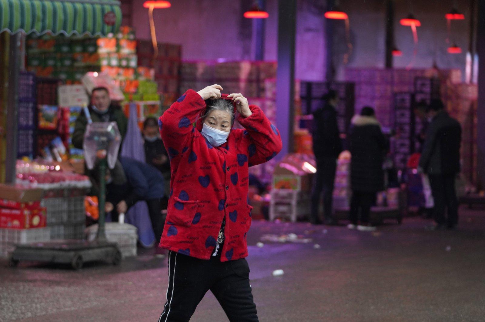 A woman wearing her mask walks past a fruit market near the Huanan Seafood Market in Wuhan, China, Jan. 31, 2021. (AP Photo)