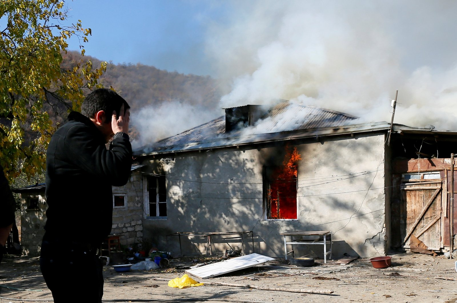 A man reacts as he stands near a house set on fire by departing ethnic Armenians, in an area that had held under their military control but is soon to be turned over to Azerbaijan, in the village of Cherektar in the region of Nagorno-Karabakh, Nov. 14, 2020. (REUTERS)