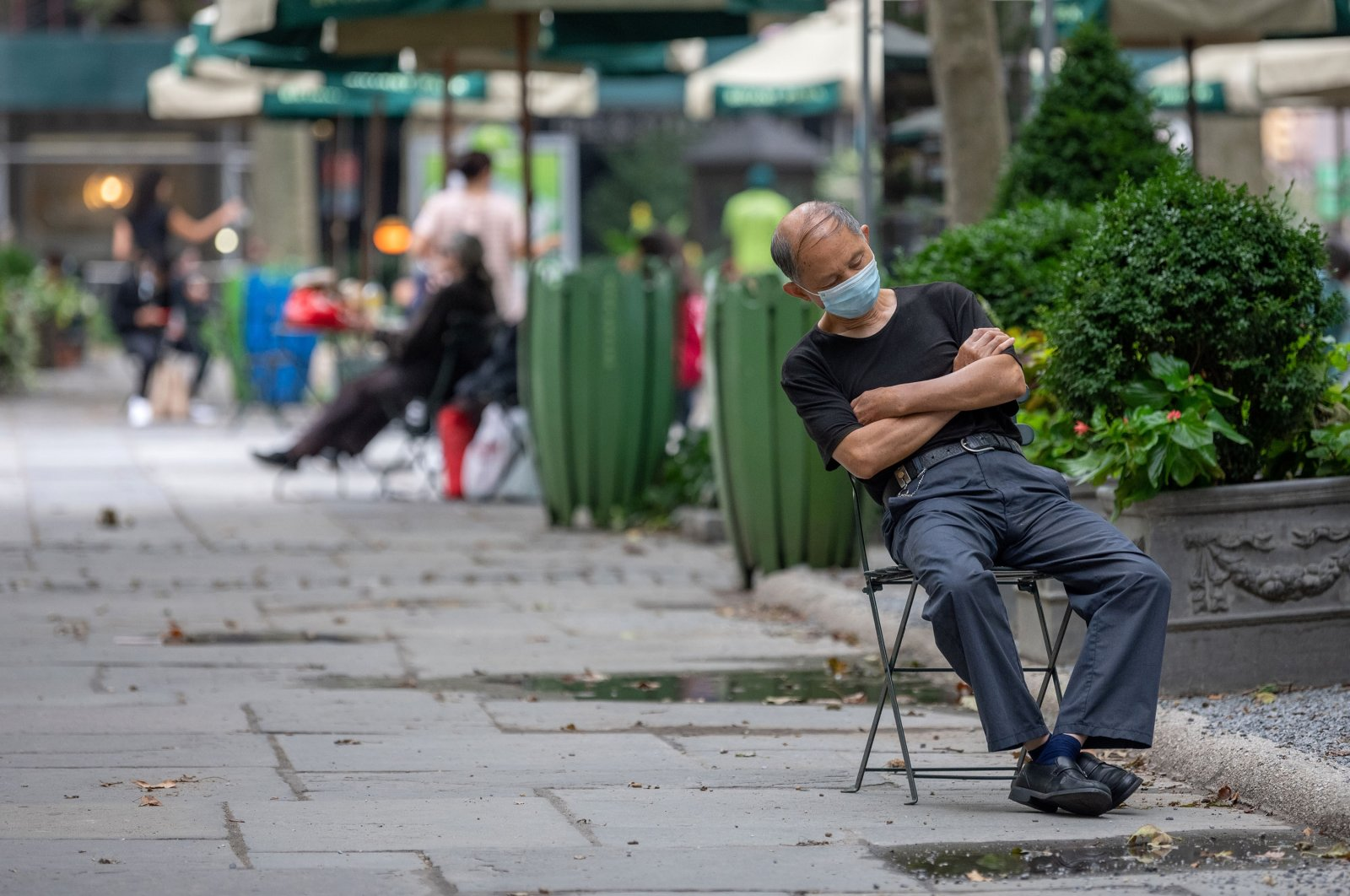 A man wearing a mask takes a nap while sitting in Bryant Park in New York City, U.S., Aug. 7, 2020. (Getty Images)