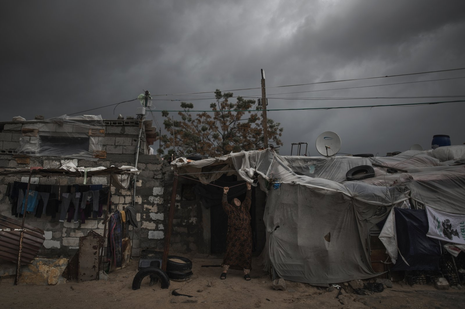 A Palestinian woman checks the nylon cover on the roof of her house on a rainy day in a poor neighborhood of Khan Younis, in the southern Gaza Strip, Jan. 20, 2021. (AP File Photo)