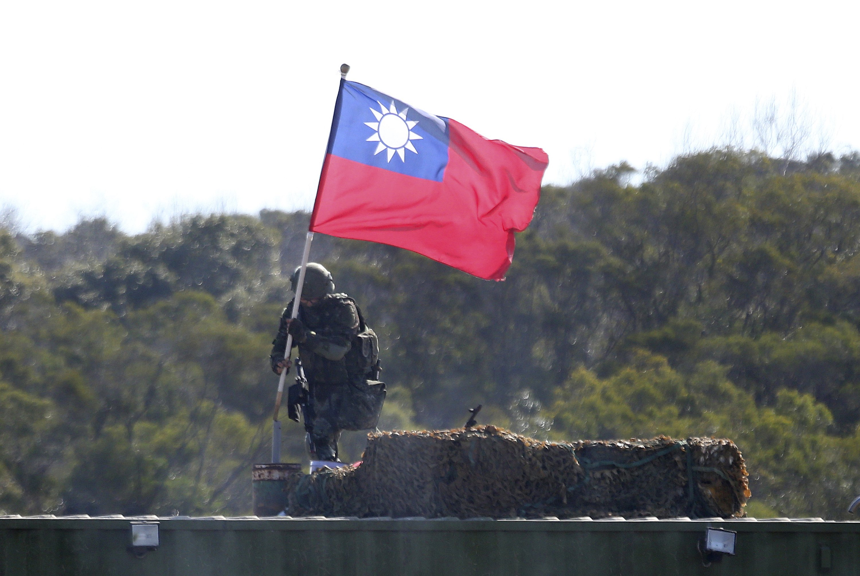 A soldier holds a Taiwanese national flag during a military exercise in Hsinchu County, northern Taiwan, Jan. 19, 2021. (AP Photo)