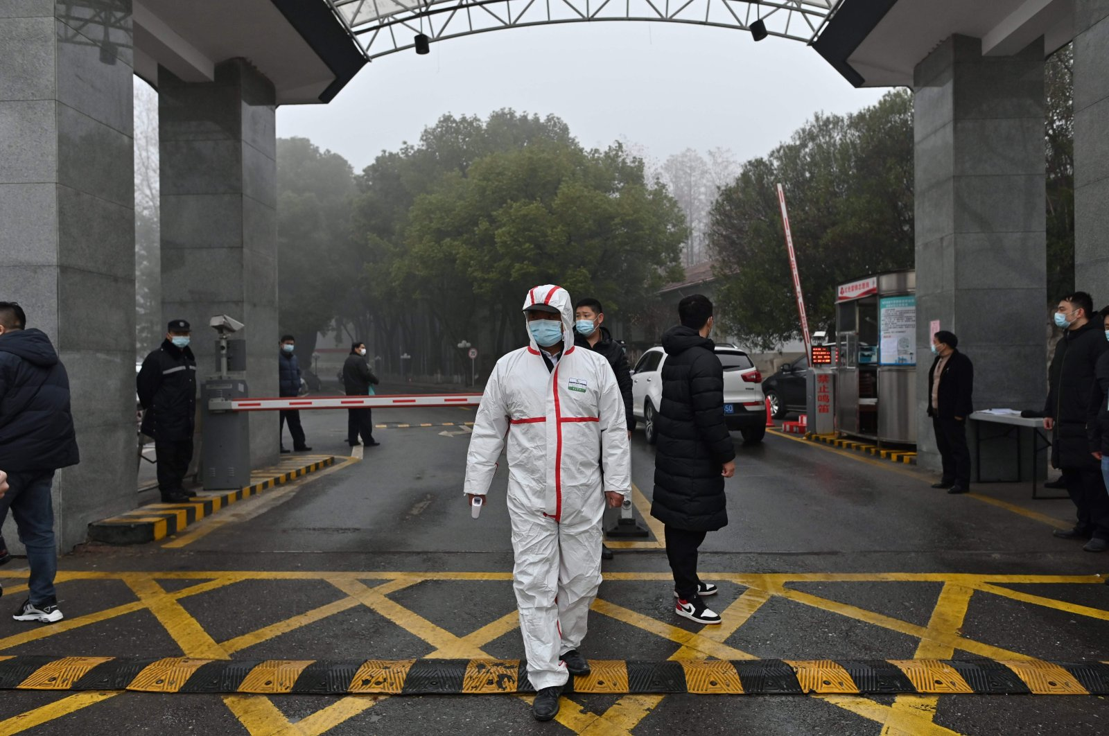 A guard wearing protective gear is at the entrance of the Hubei Provincial Center for Disease Control (Hubei CDC) while members of the World Health Organization (WHO) team investigating the origins of the coronavirus visit the place, Wuhan, Hubei province, central China, Feb. 1, 2021. (AFP Photo)