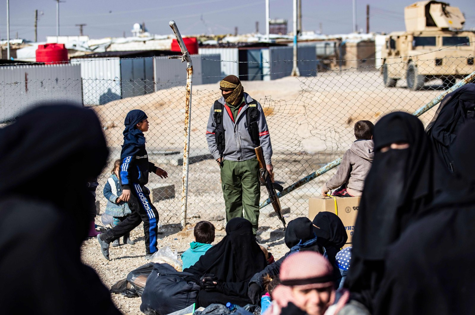 A YPG terrorist group member stands guard as women lead children ahead of departure during the release of another group of Syrian families from the al-Hol camp, which holds suspected relatives of Daesh fighters, in the al-Hasakah governorate, northeastern Syria, Jan. 28, 2021. (AFP Photo)