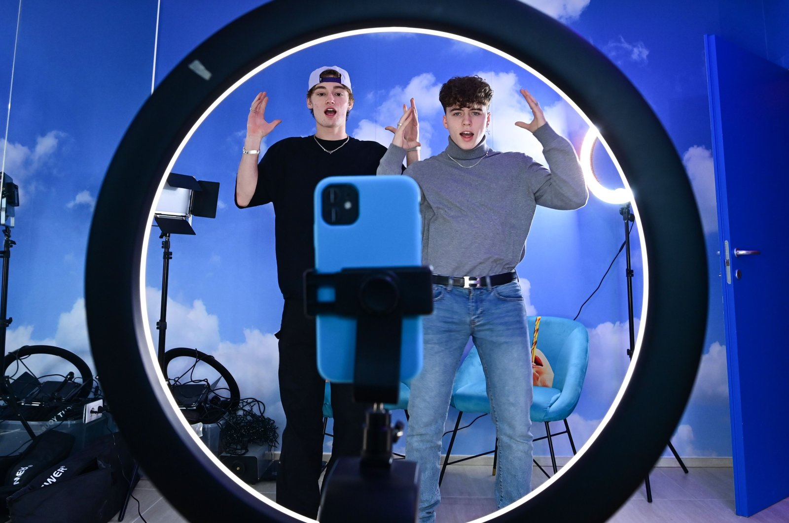 "(L-R) TikTok influencers Marco Bonetti and Davide Moccia perform a video in the ""Defhouse"", a TikTok influencers incubator in Milan, on January 21, 2021. (AFP Photo)"