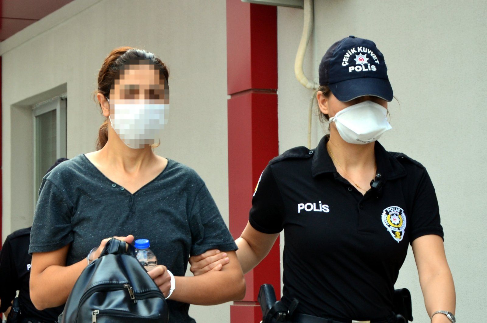 A police officer takes Zeynep T. to the police station in Adana, Turkey, Feb. 1, 2021. (DHA)