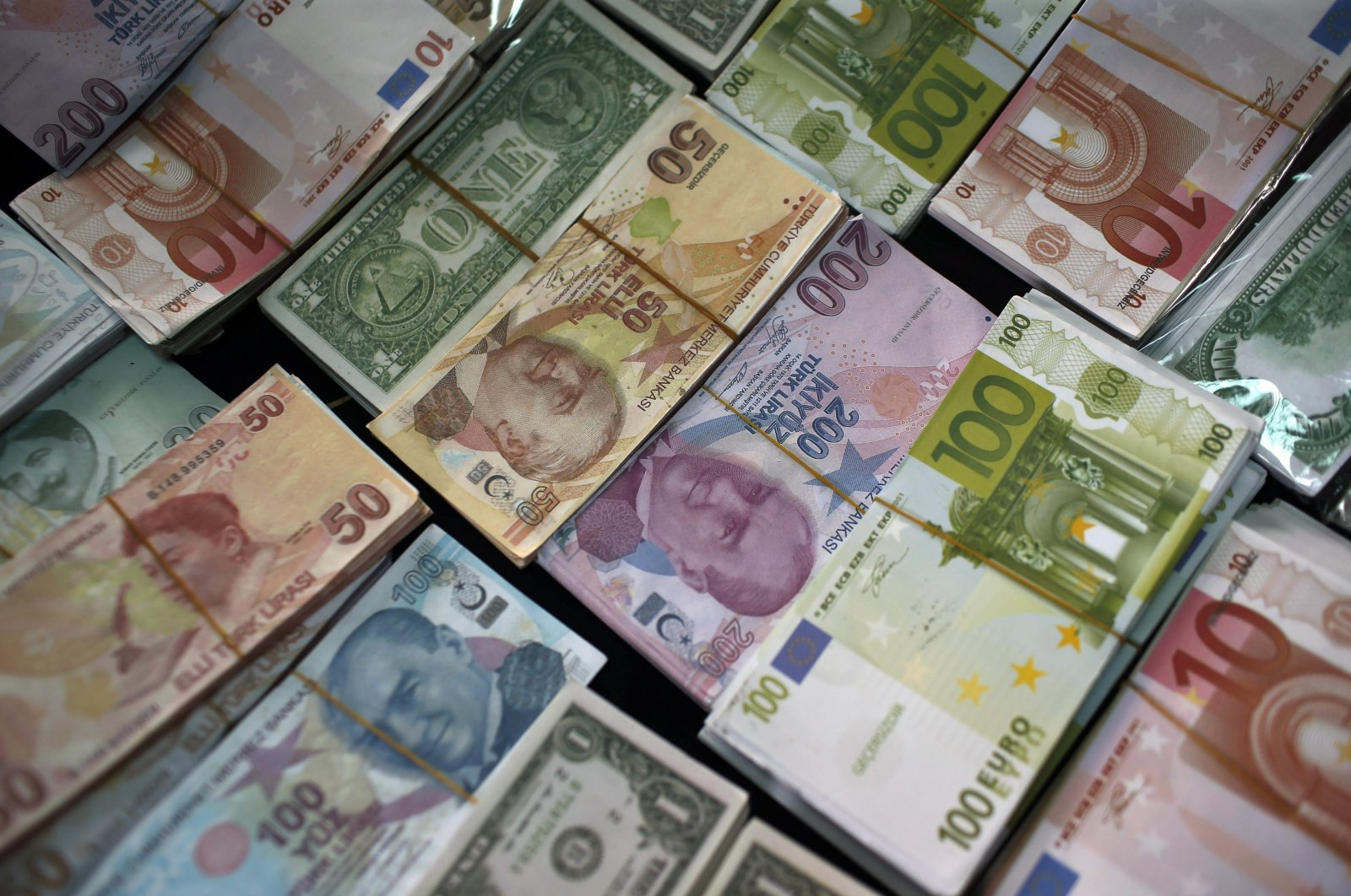 Turkish liras, euros and U.S. dollars are stacked at a currency exchange office in Istanbul, Turkey.  June 8, 2015. (AP Photo)