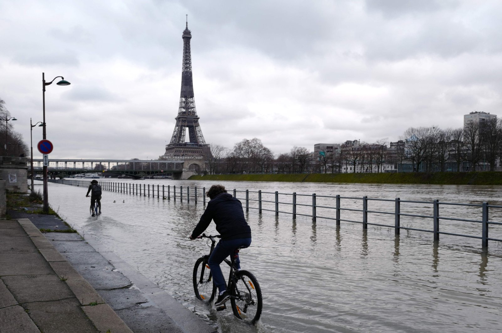 People ride bikes along the Seine river as it overflows in Paris, on Feb. 1, 2021. (AFP Photo)