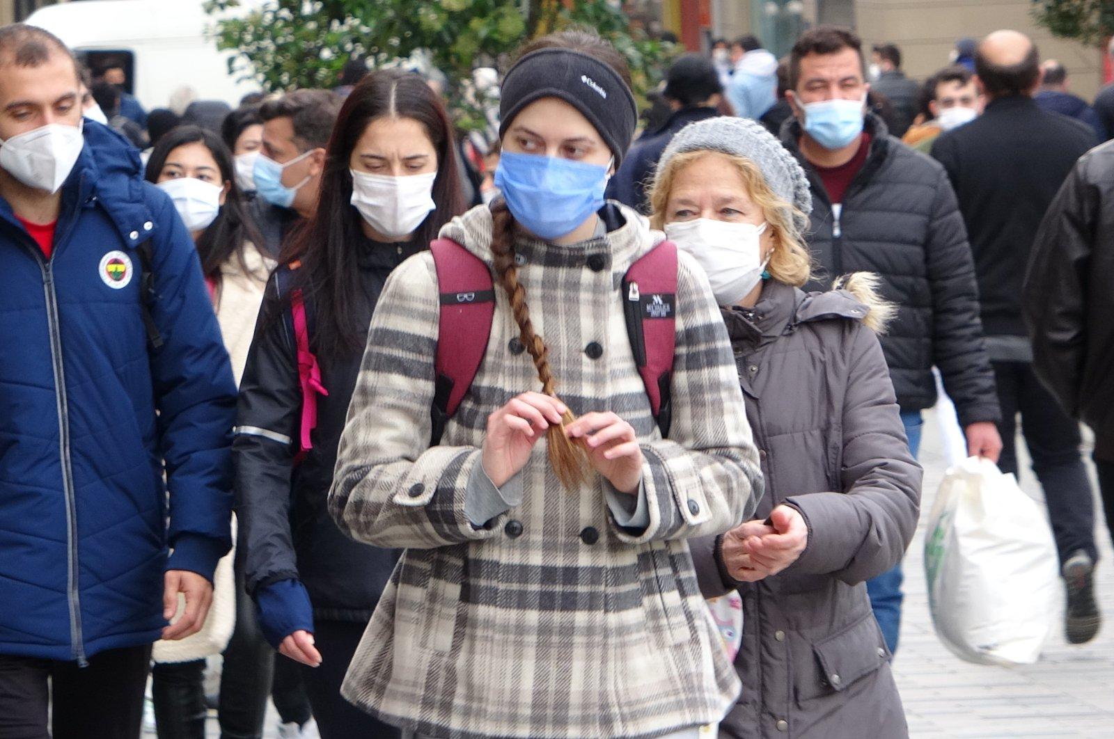 People wearing masks take a walk in Istanbul's Taksim Square on Feb. 1, 2021 (IHA Photo)