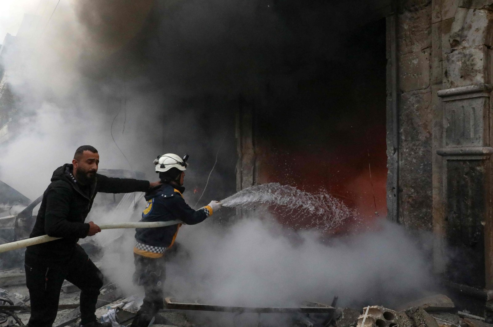 Rescue workers extinguish a fire caused by a suspected YPG terrorist attack in the town of Azaz in the opposition-controlled northern countryside of Syria's Aleppo province, Jan. 31, 2021. (AFP Photo)