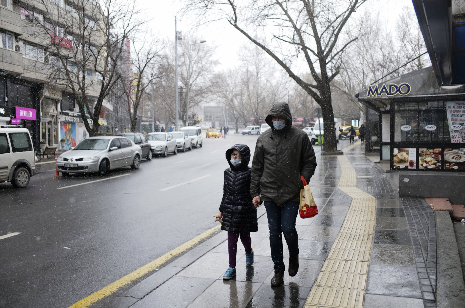 A man and a child wearing protective masks walk on a street in the capital Ankara, Turkey, Jan. 30, 2021. (AP PHOTO)