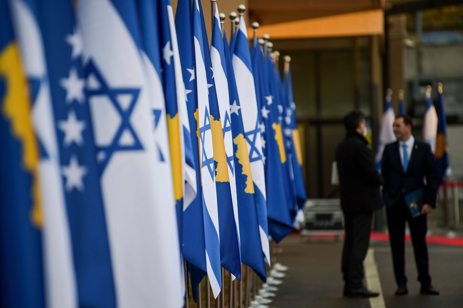 Kosovo's government officials stand in front of the flags of Kosovo and Israel, displayed during a ceremony at the headquarters of the Foreign Ministry in Pristina, Kosovo, Feb. 1, 2021. (AFP Photo)