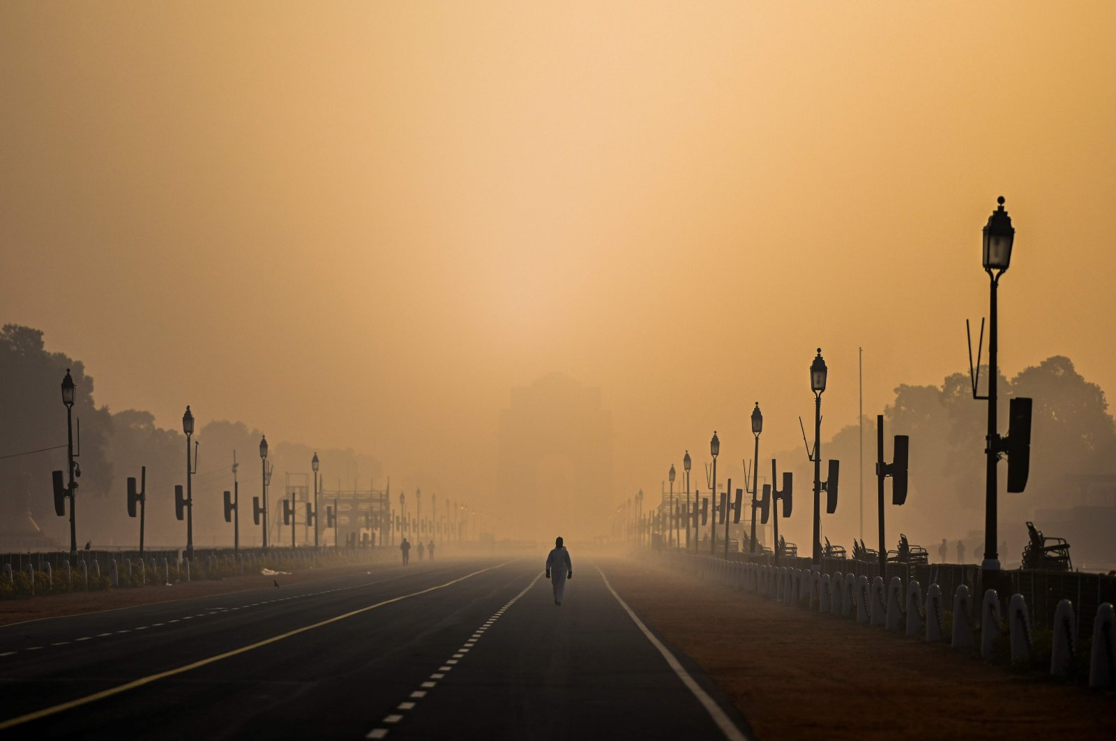 A man walks along in Rajpath as the city is blanketed under a fog caused by air pollution, New Delhi, India, Jan. 28, 2021. (AFP Photo)