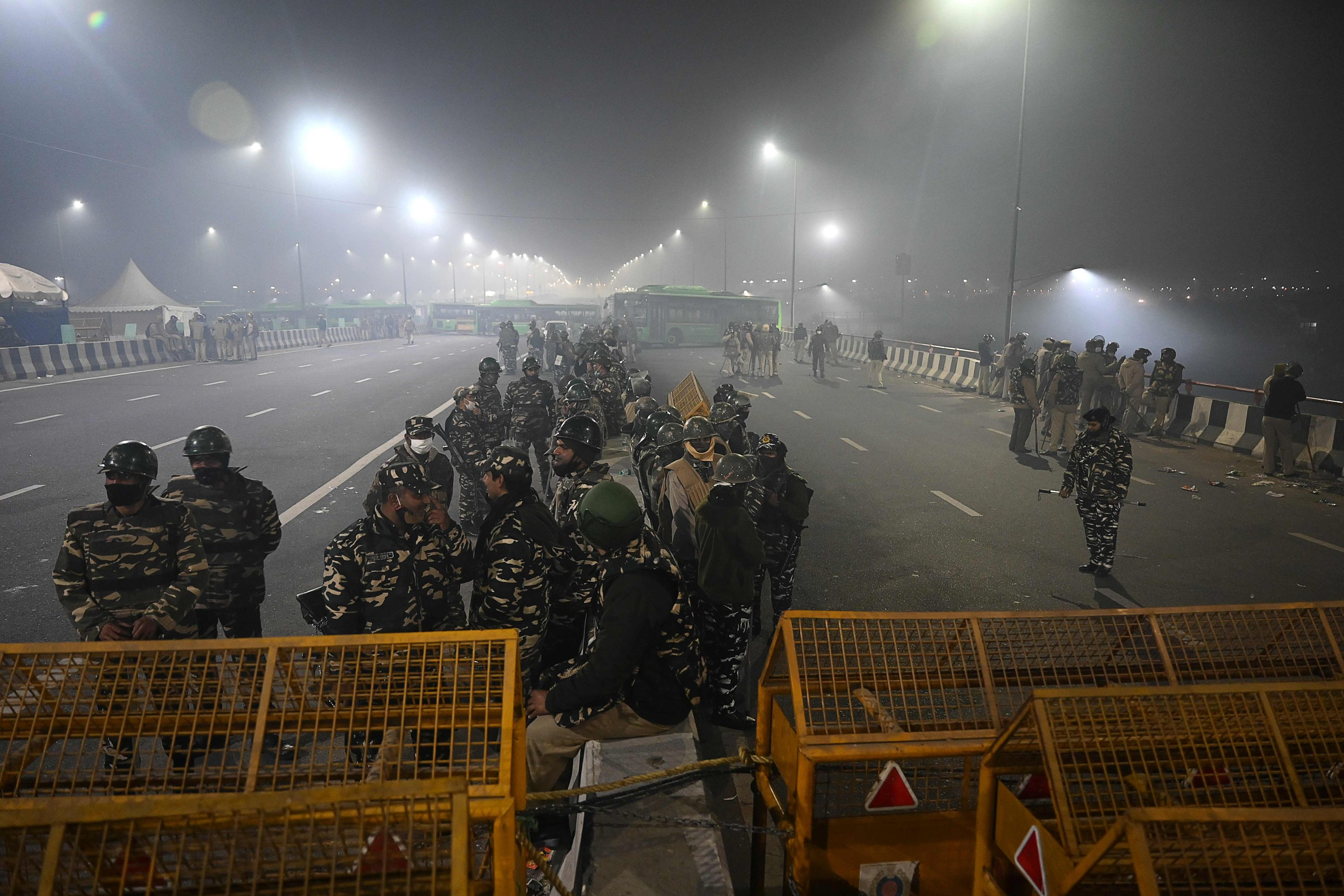 Police personnel stand guard next to barricades along a blocked highway as farmers continue to protest against the agricultural reforms, Ghazipur, India, Jan. 28, 2021. (AFP Photo)