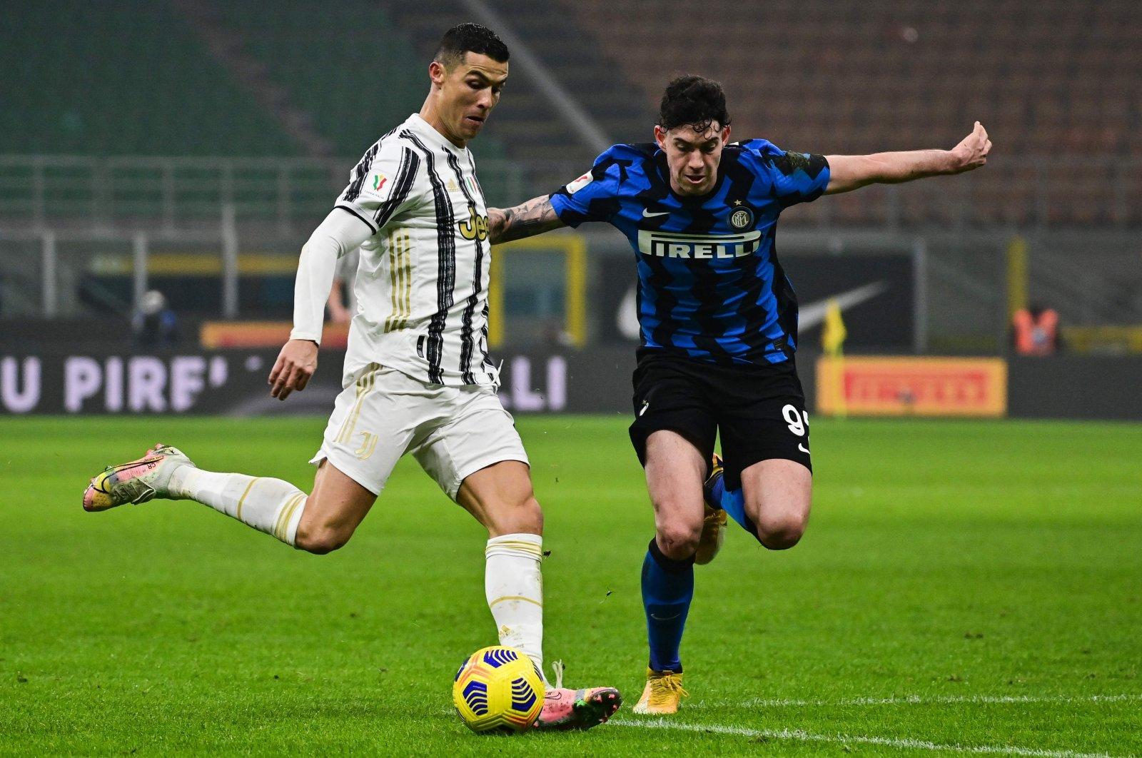 Juventus forward Cristiano Ronaldo (L) challenges Inter Milan defender Alessandro Bastoni during the Italian Cup semifinal first leg at the San Siro, Milan, Italy, Feb. 2, 2021. (AFP Photo)