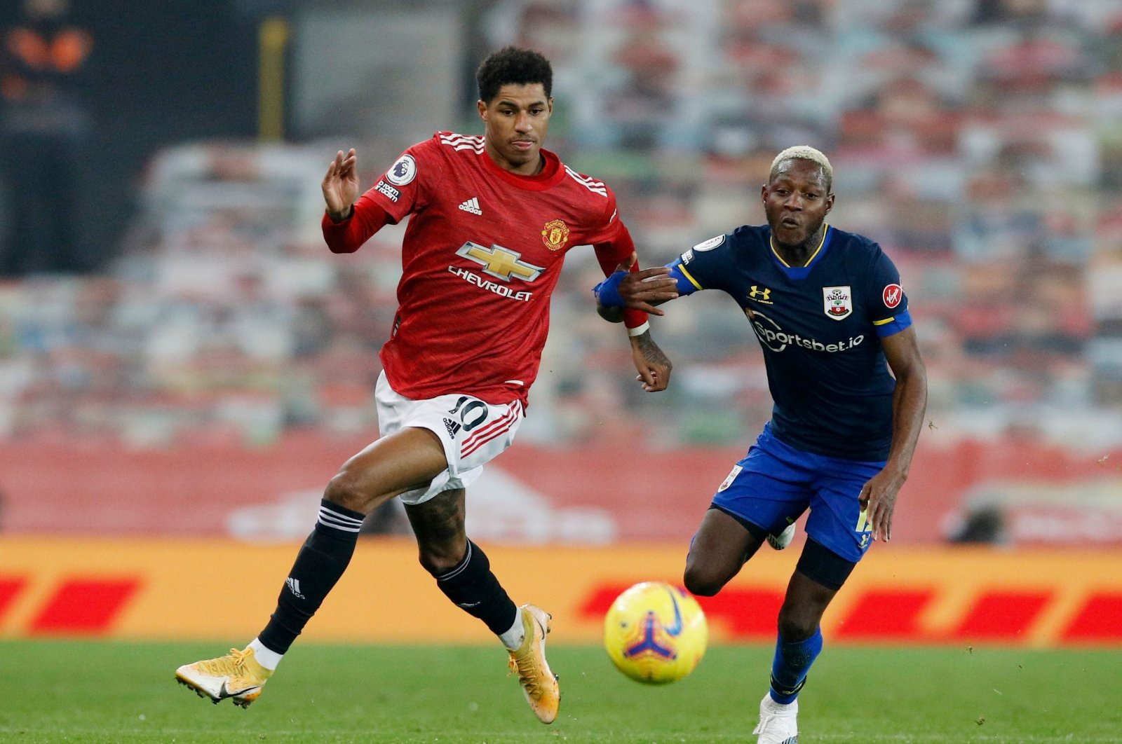 Manchester United's Marcus Rashford (L) goes past Southampton's Moussa Djenepo during their Premier League match, Old Trafford, Manchester, Feb. 2, 2021.