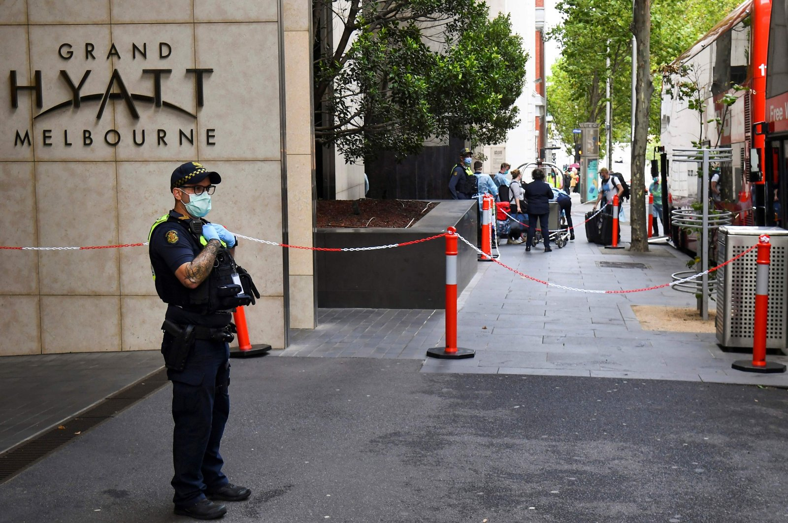 A law enforcement officer stands guard outside the Grand Hyatt hotel as tennis players and officials arrive for a two-week quarantine ahead of the Australian Open, Melbourne, Australia, Jan. 15, 2021. (AFP Photo)