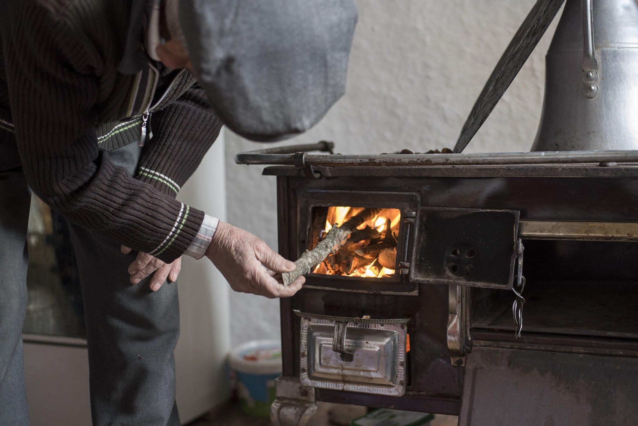 Türkiye'de yaşlı bir adam, Eskişehir'de bir kır evinde geleneksel bir Türk sobasının içine odun bırakırken görülüyor.  (Shutterstock görselleri)