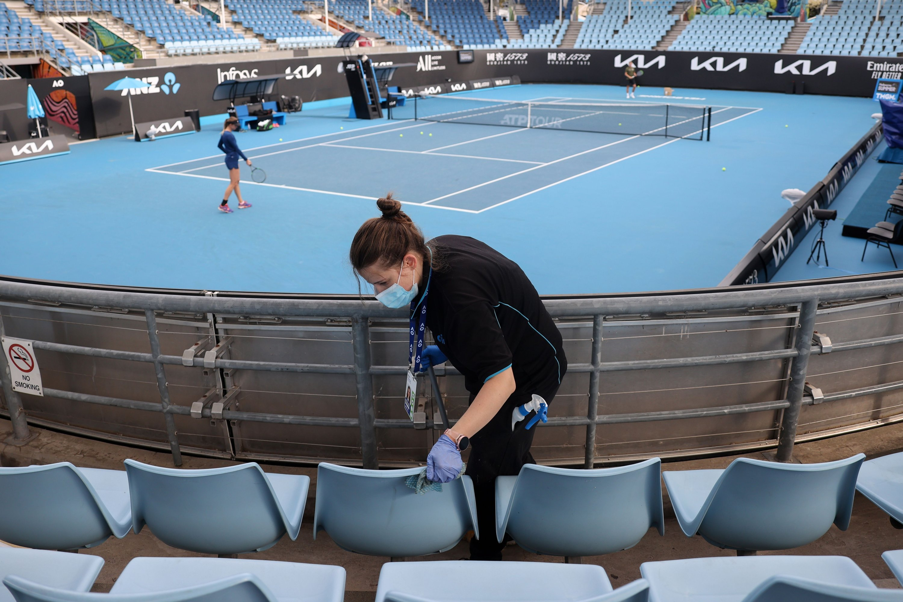 A worker cleans the seating areas on court 3 during a warmup session at Melbourne Park in Melbourne, Feb. 4, 2021. (AFP Photo)