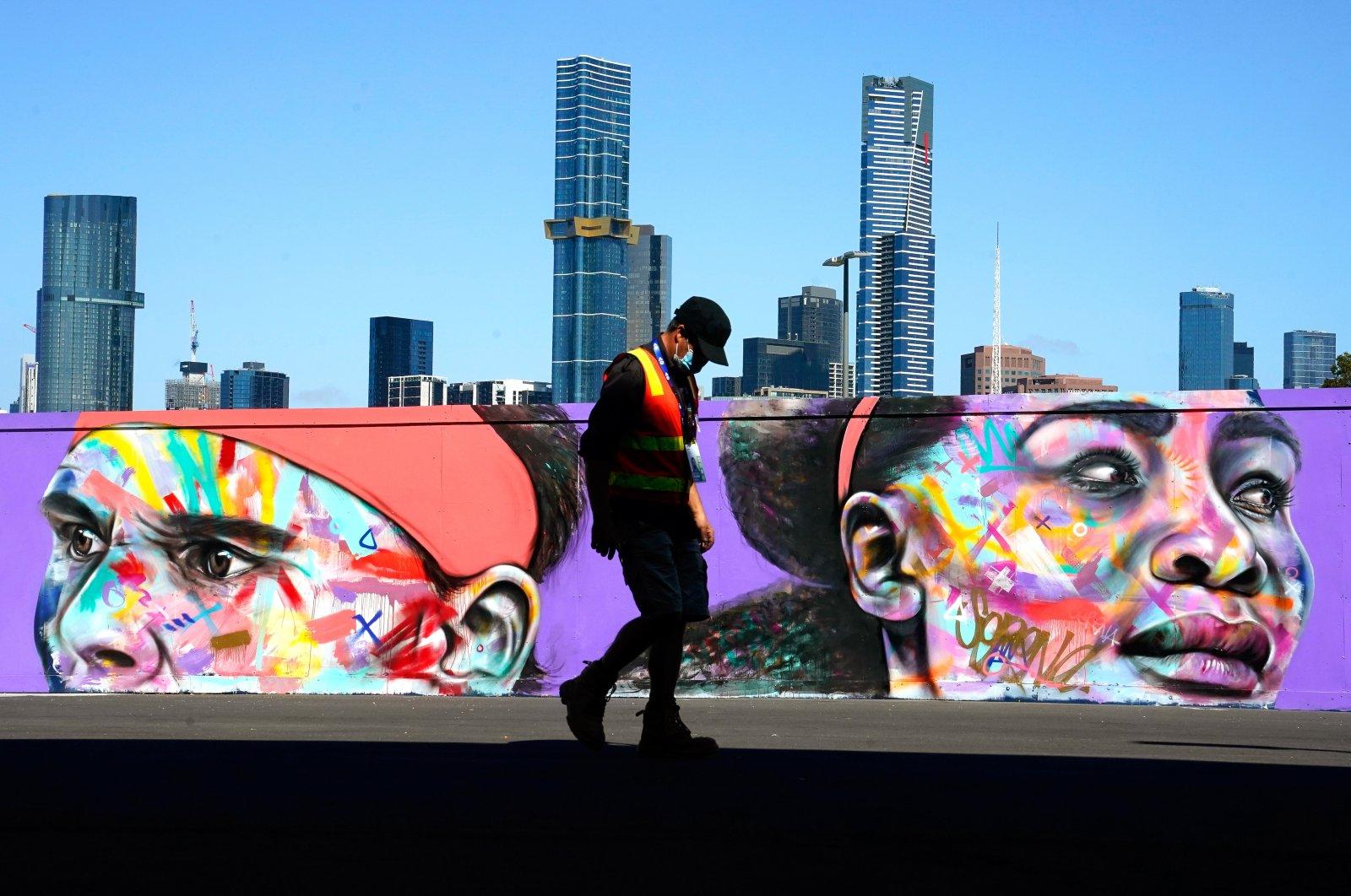 A worker in a protective face mask walks inside the Melbourne Park tennis precinct in Melbourne, Australia, Feb. 3, 2021. (EPA Photo)
