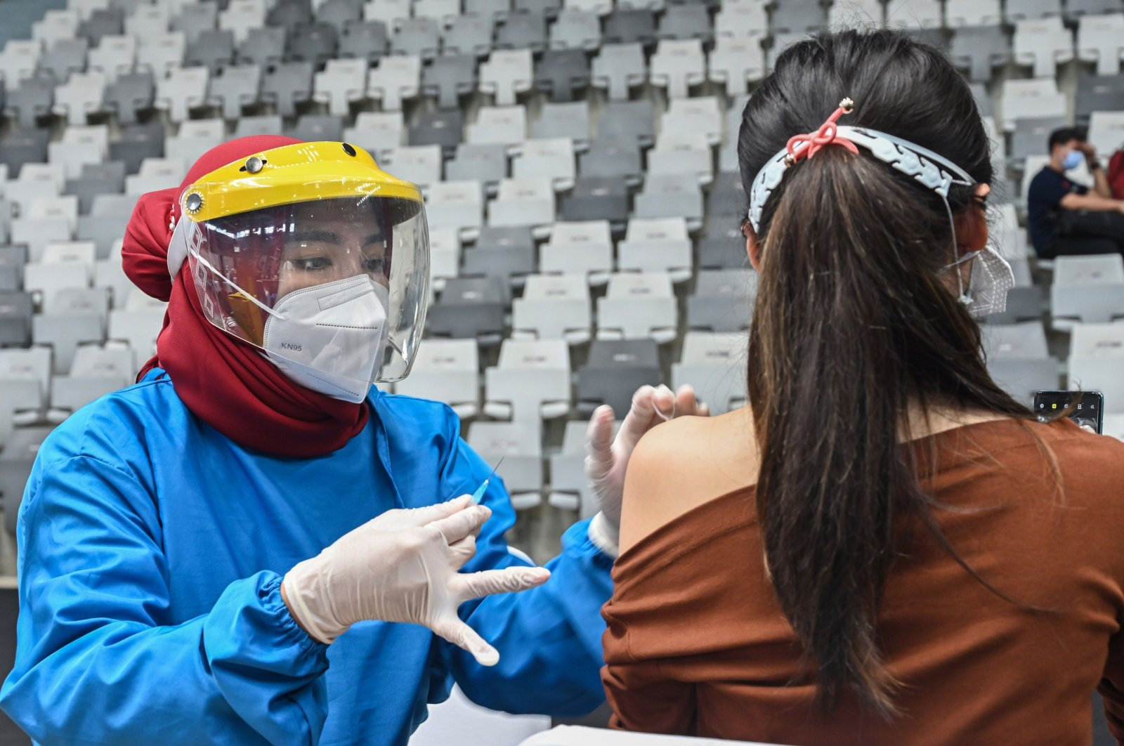 A health worker (R) receives a vaccine for COVID-19 at Istora Senayan stadium in Jakarta, Indonesia, Feb. 4, 2021. (AFP Photo)