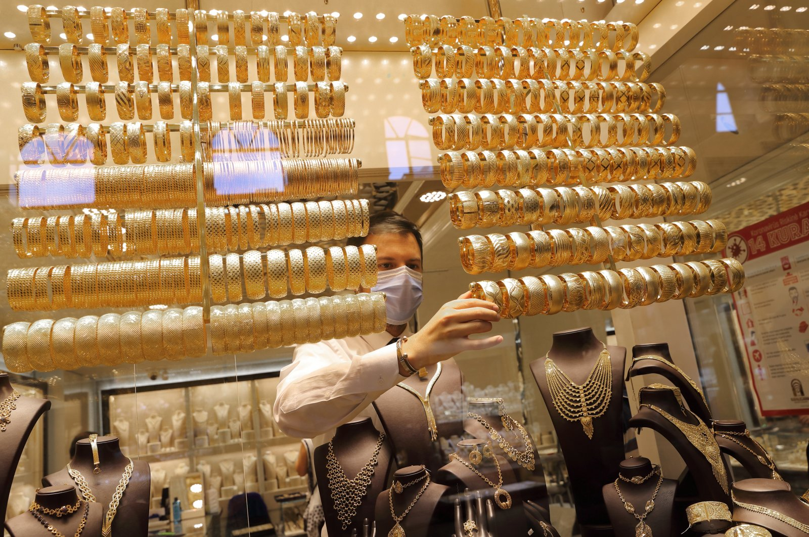 A goldsmith wearing a protective mask arranges golden bangles at a jewelry shop at the Grand Bazaar in Istanbul, Turkey, Aug. 6, 2020. (Reuters Photo)