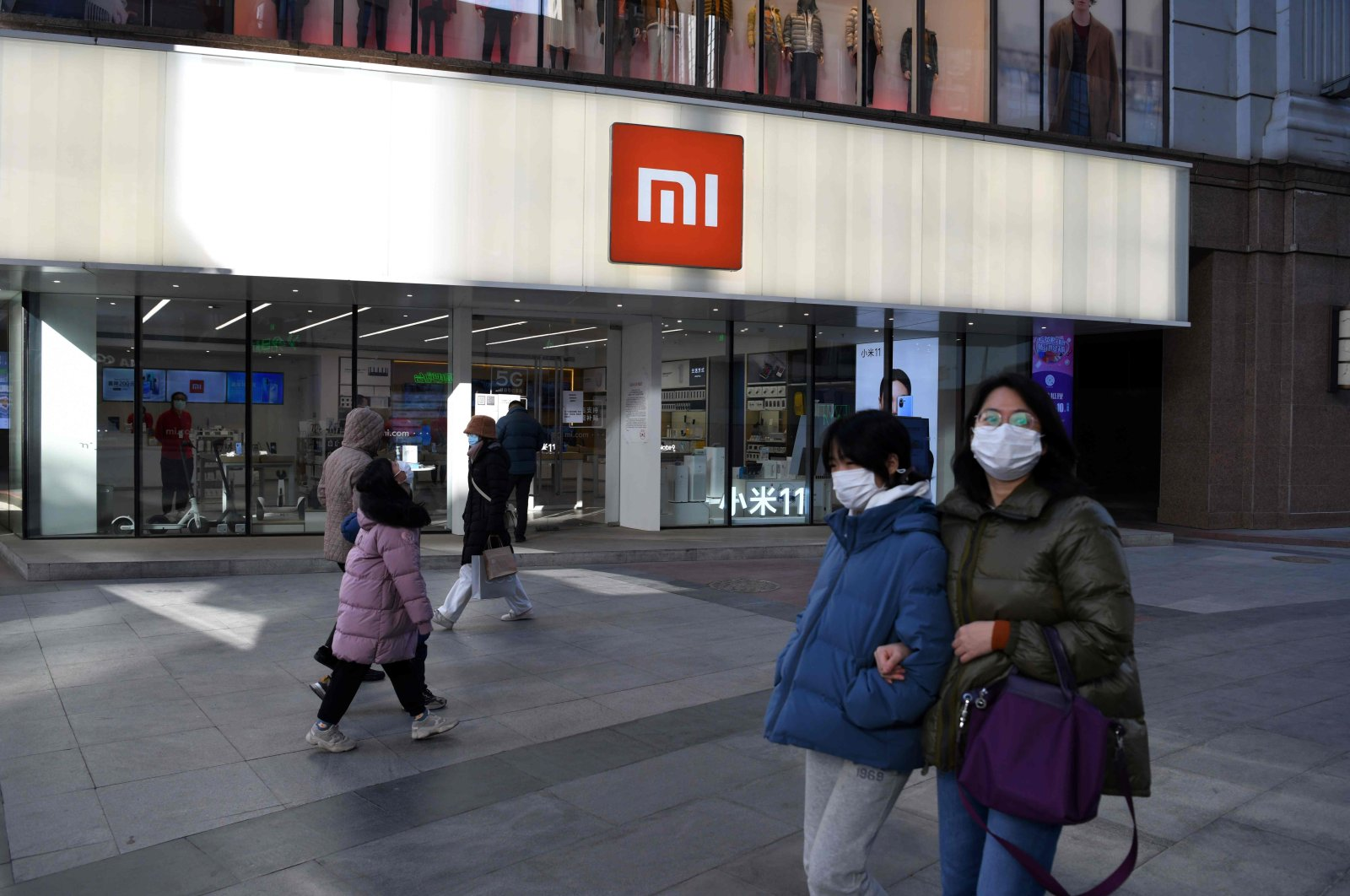 In this file photo, people walk past a Xiaomi store in Beijing, China, Jan. 15, 2021. (AFP Photo)