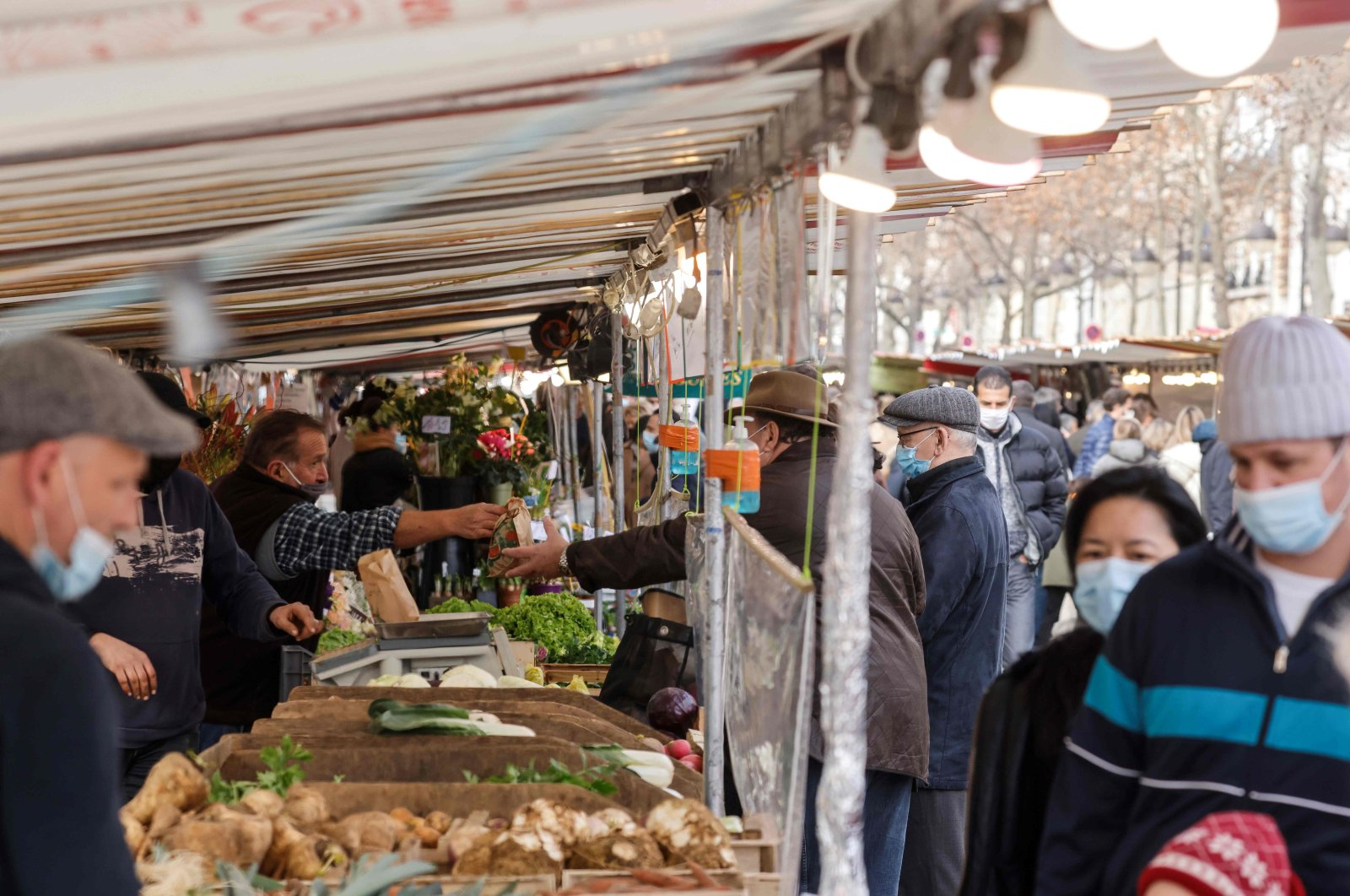 A market stand is protected by see-through plastic sheets to keep a distance between the seller and buyer, as people wearing protective face masks visit the weekly market to shop for vegetables, fruits and dairy products in Paris, France, Jan. 30, 2021. (AFP Photo)