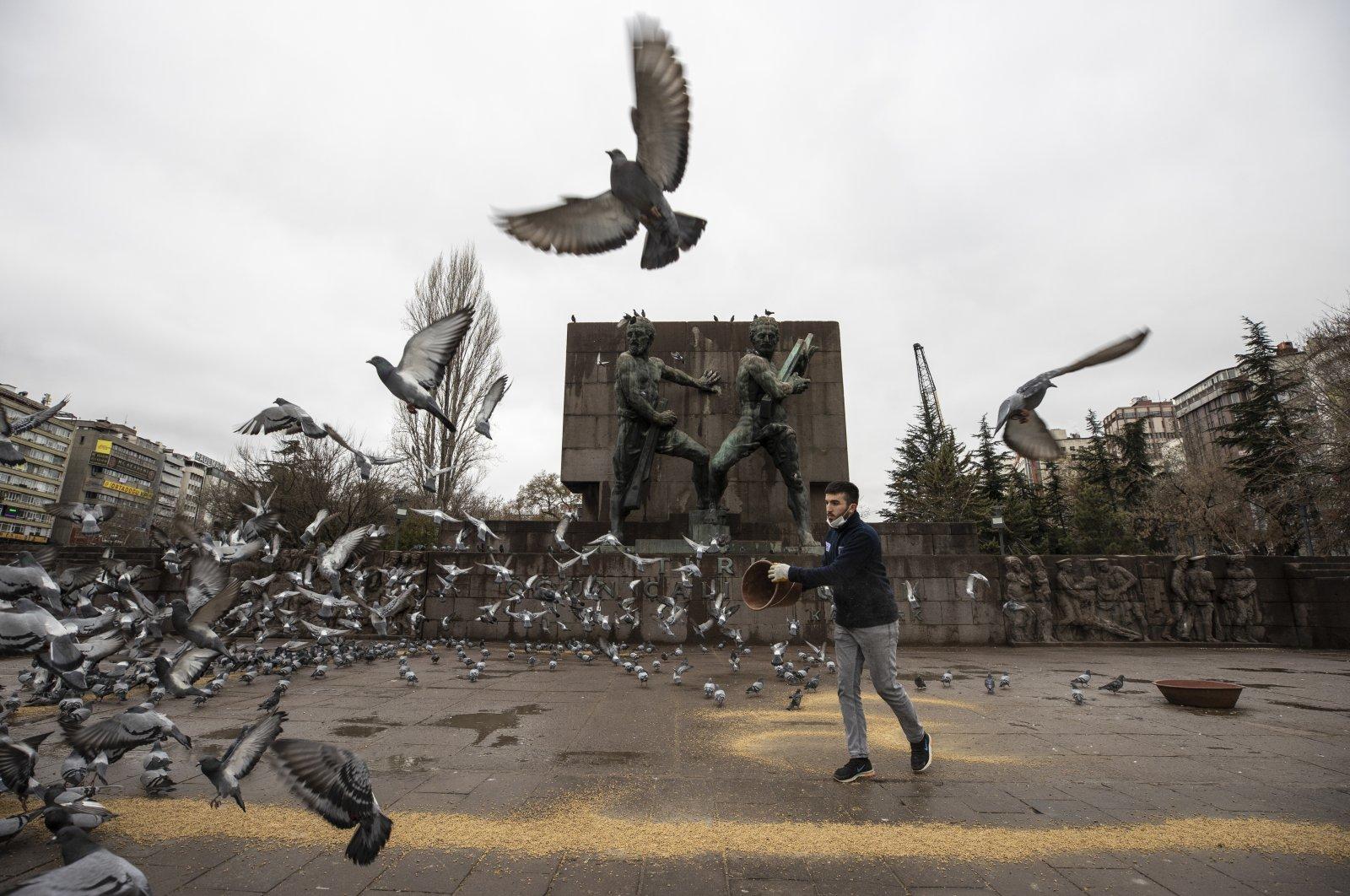 A man feeds birds at the July 15 Kızılay National Will Square in Ankara, Turkey, Jan. 1, 2021. (AA)