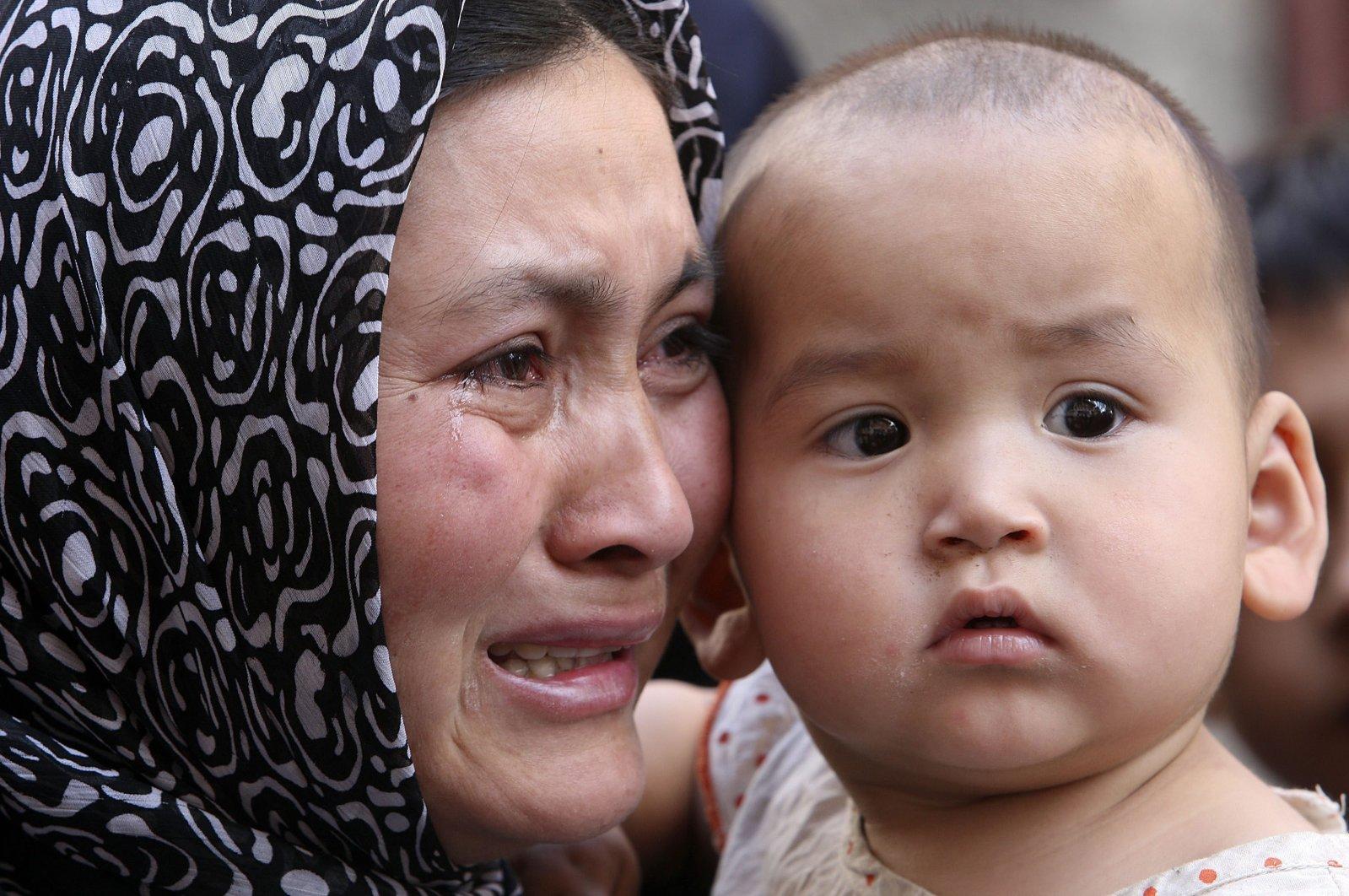 A Uighur woman cries as reporters visit a Uighur district that protested in Urumqi, Xinjiang Uighur Autonomous Region, western China, July 9, 2009. (AP Photo/Eugene Hoshiko)